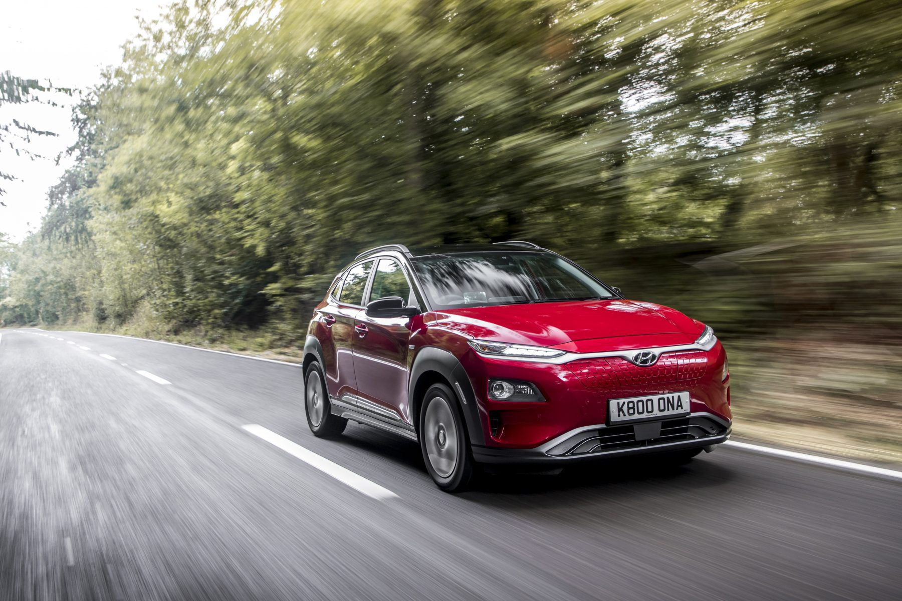 Red Hyundai Konda Electric driving on a road