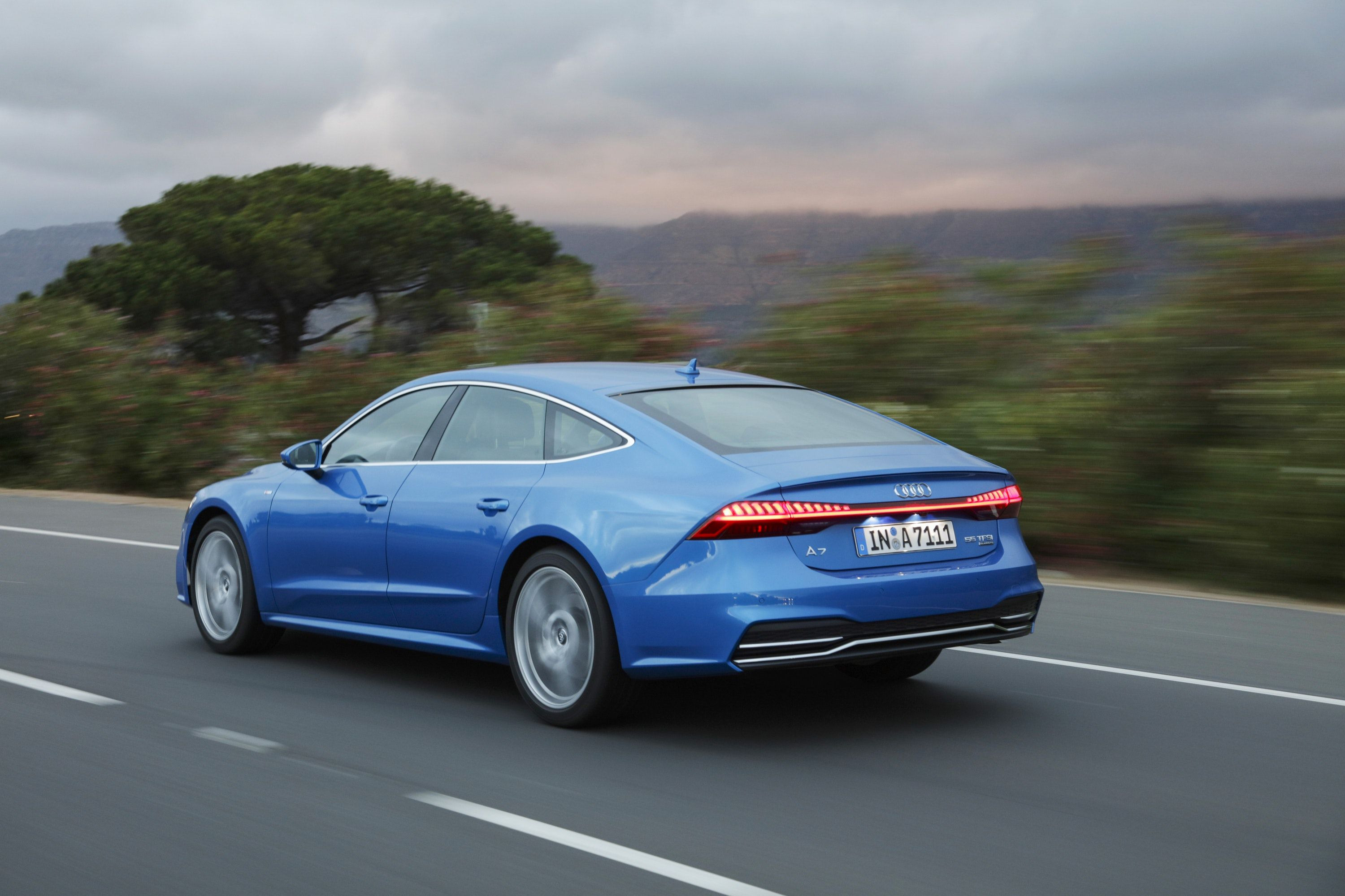 rear view of blue Audi A7 Sportback driving on a road