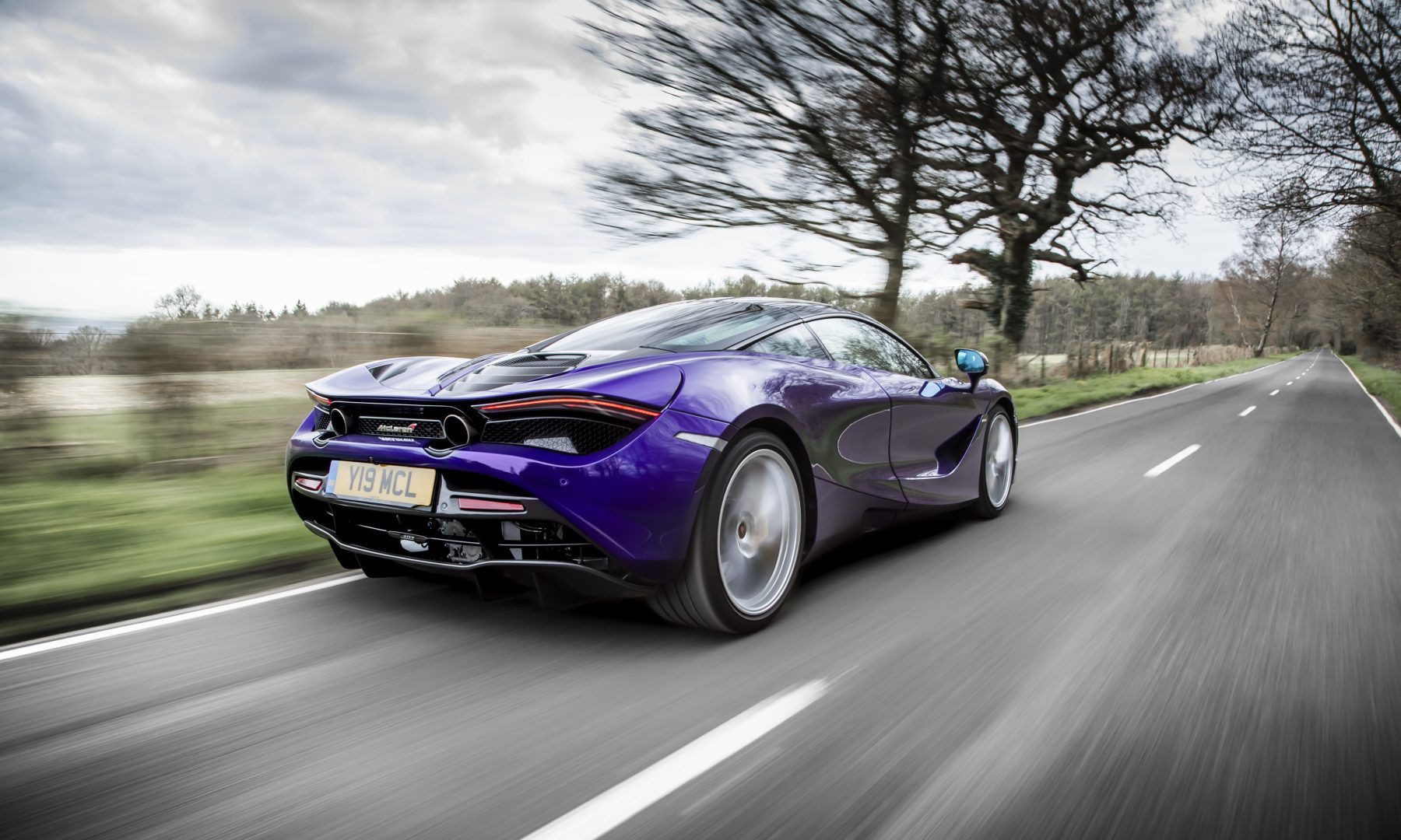 A Blue McLaren 720S driving in the countryside
