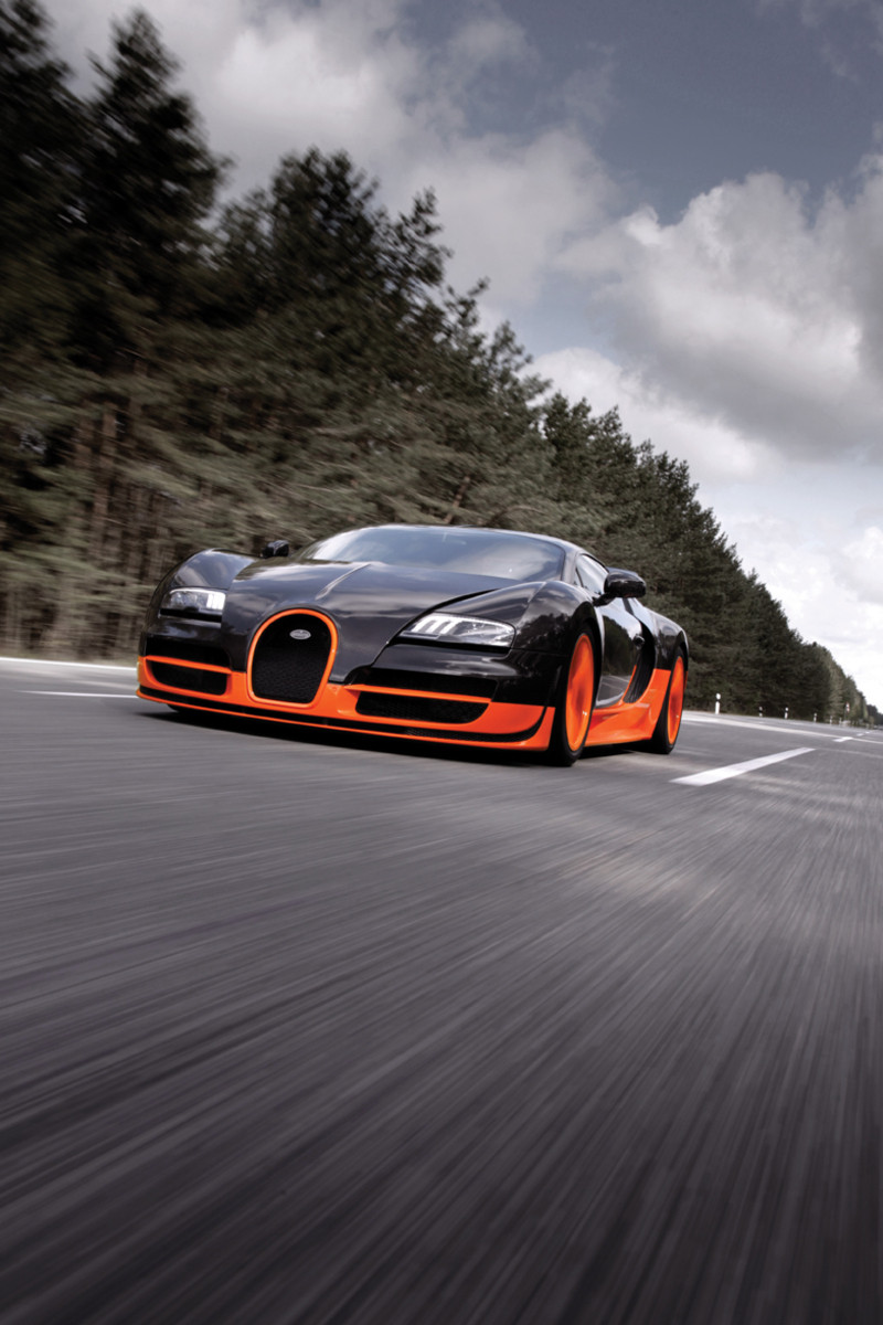 Black and orange Bugatti Veyron Super Sport speeding down a road towards you