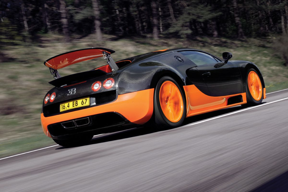 Black and organge Bugatti Veyron Super Sport driving fast down a road away from you