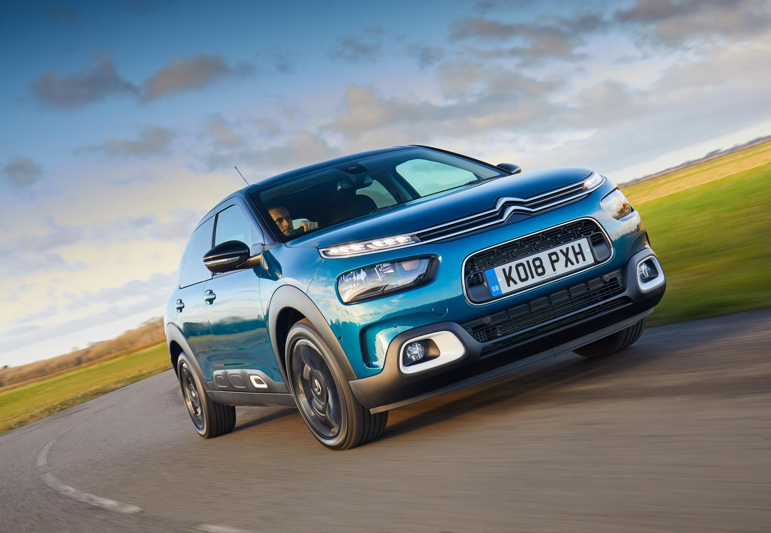 Bright blue metallic Citroen C4 Cactus driving towards you very close up