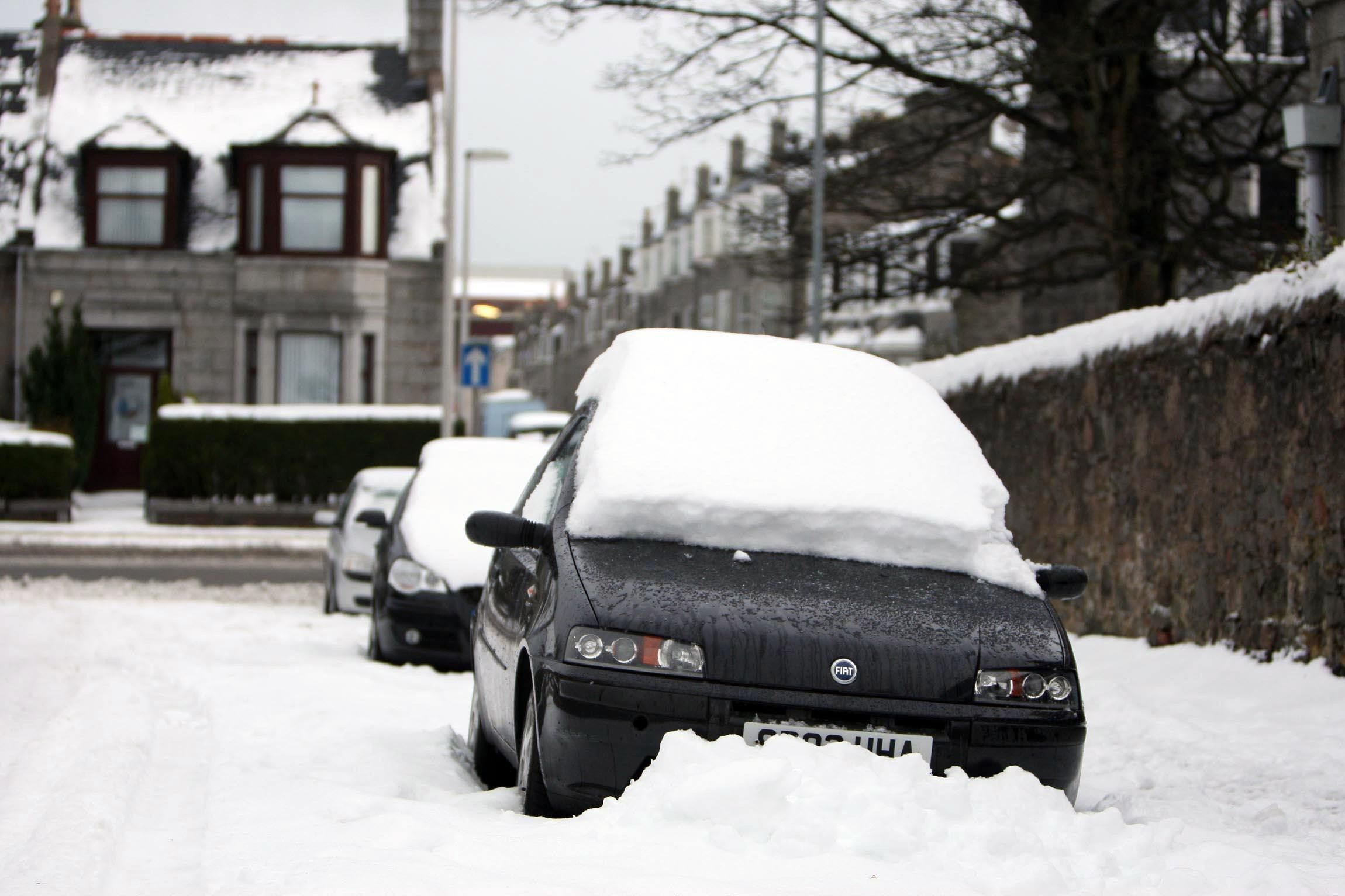 Car parked on the side of the road covered in snow