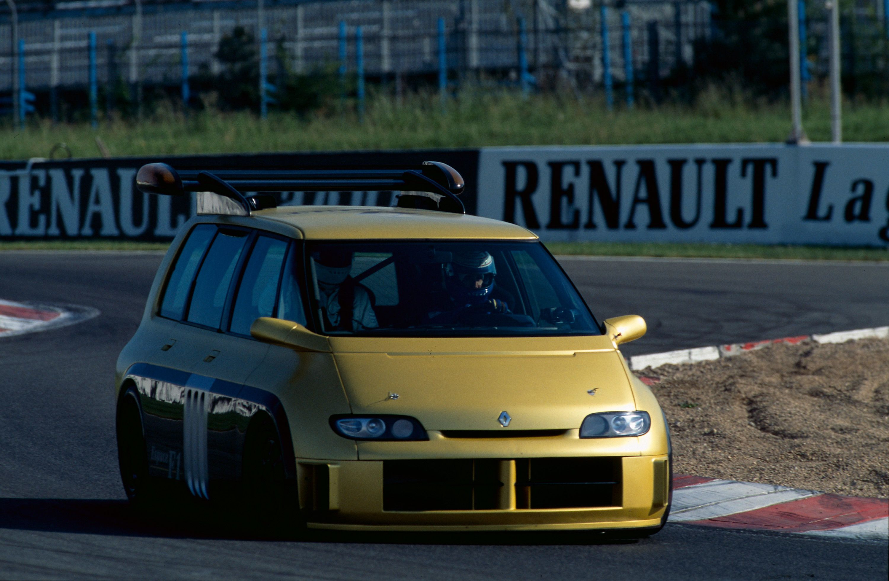 Gold Renault Espace modified into a track car with sports kit driving on a track