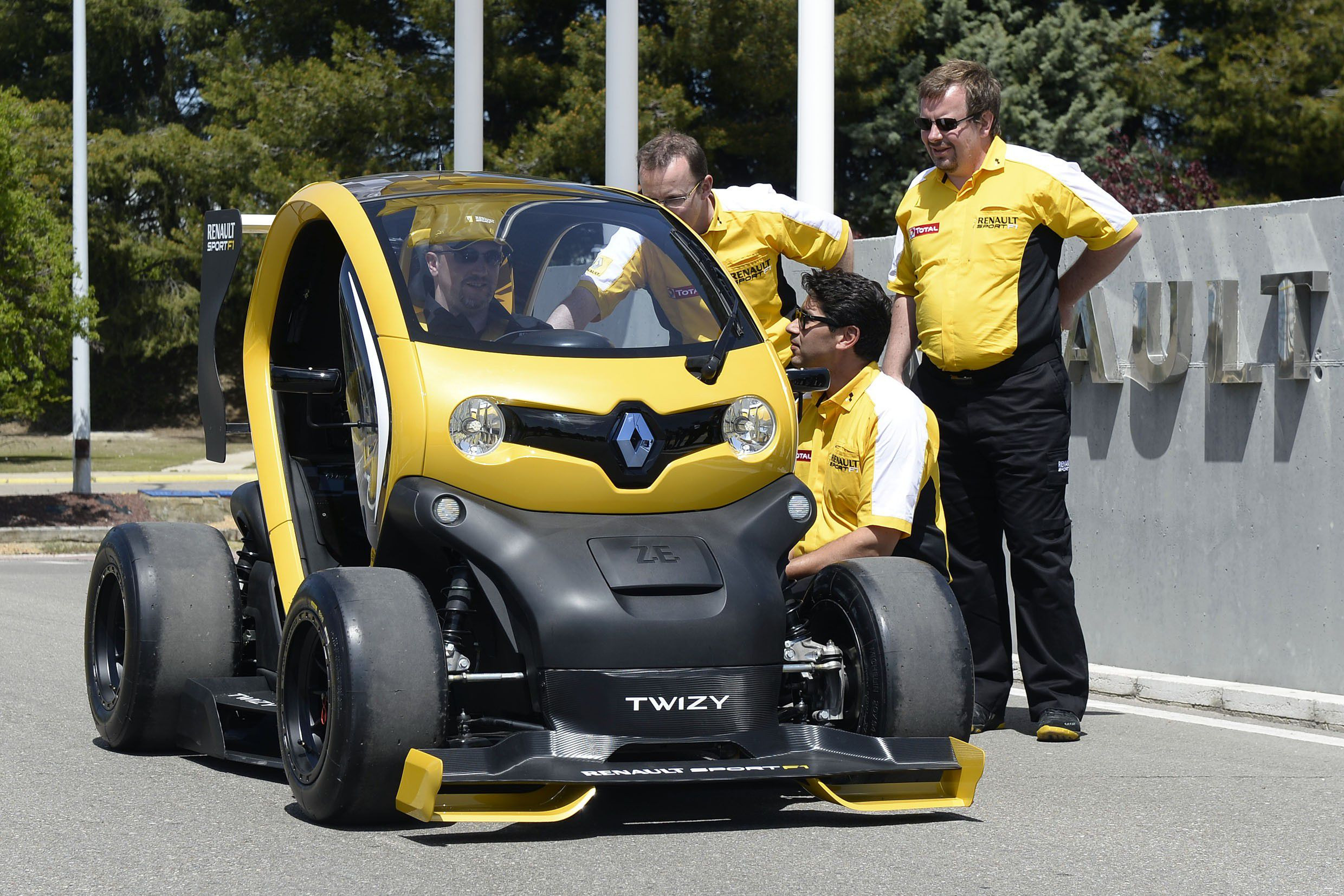 Black and yellow Renault Twizy with a man in it and three man stood at the side of it talking to the man inside.