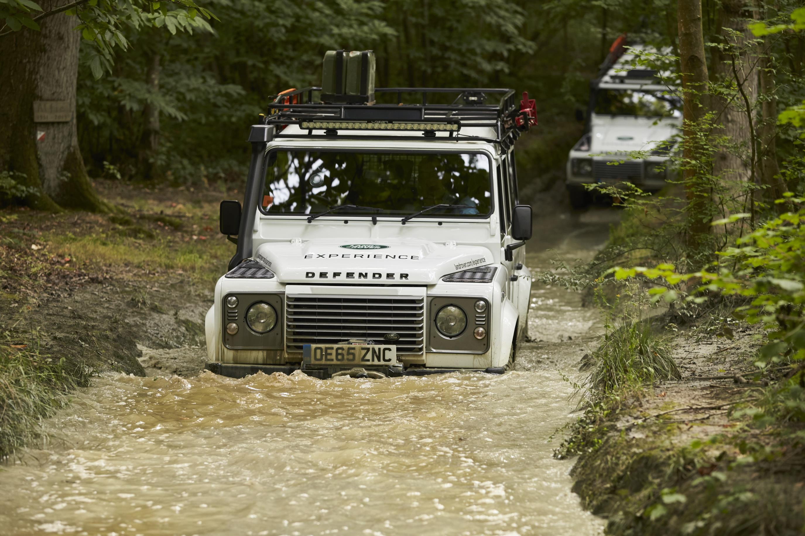 White Land Rover Defender driving through a stream