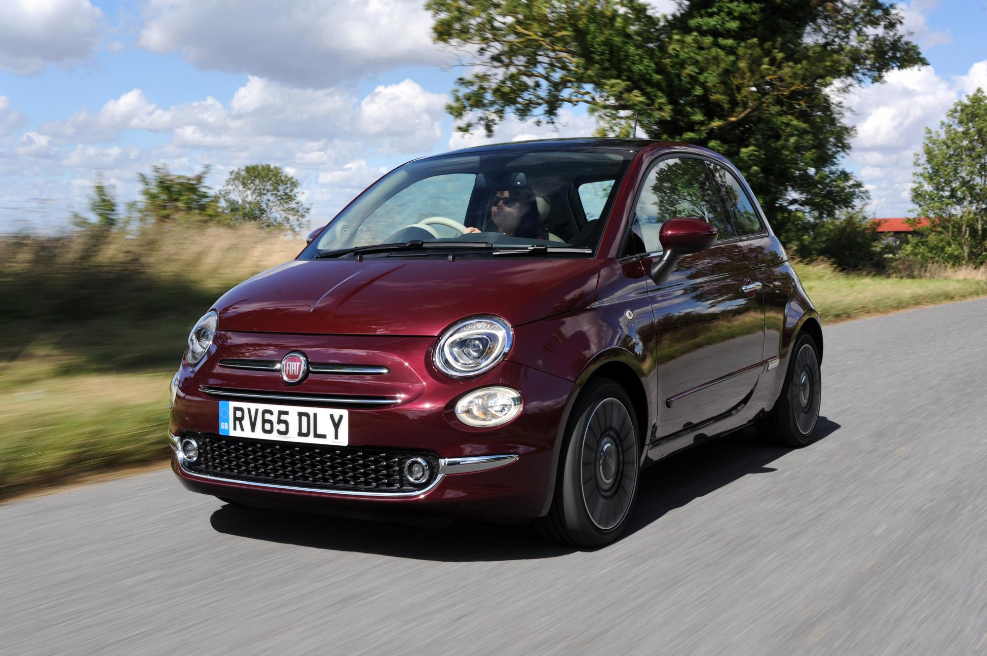 Close up of a burgundy coloured Fiat 500 driving towards you down a country lane