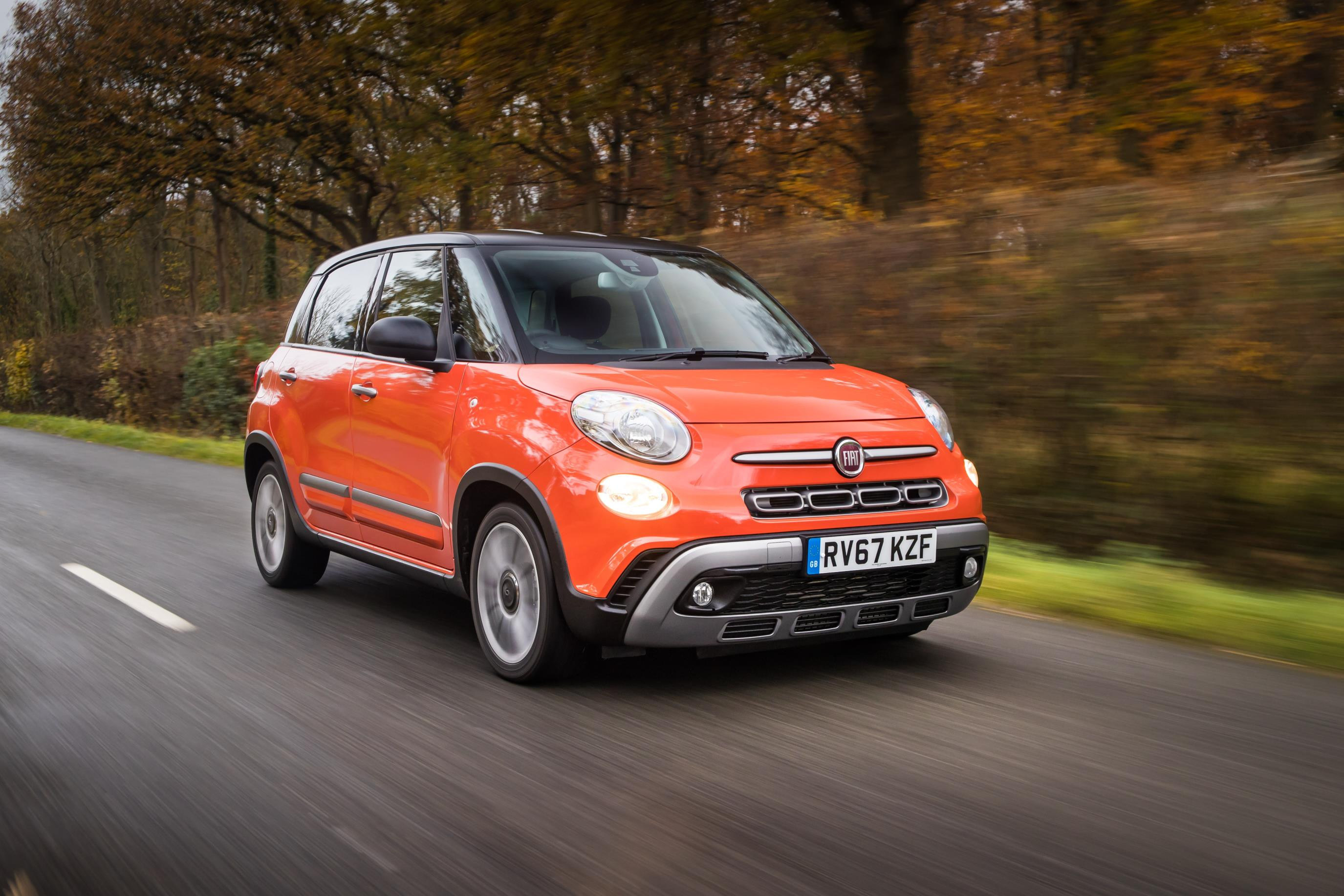 Orange Fiat 500L driving down a leafy road towards you