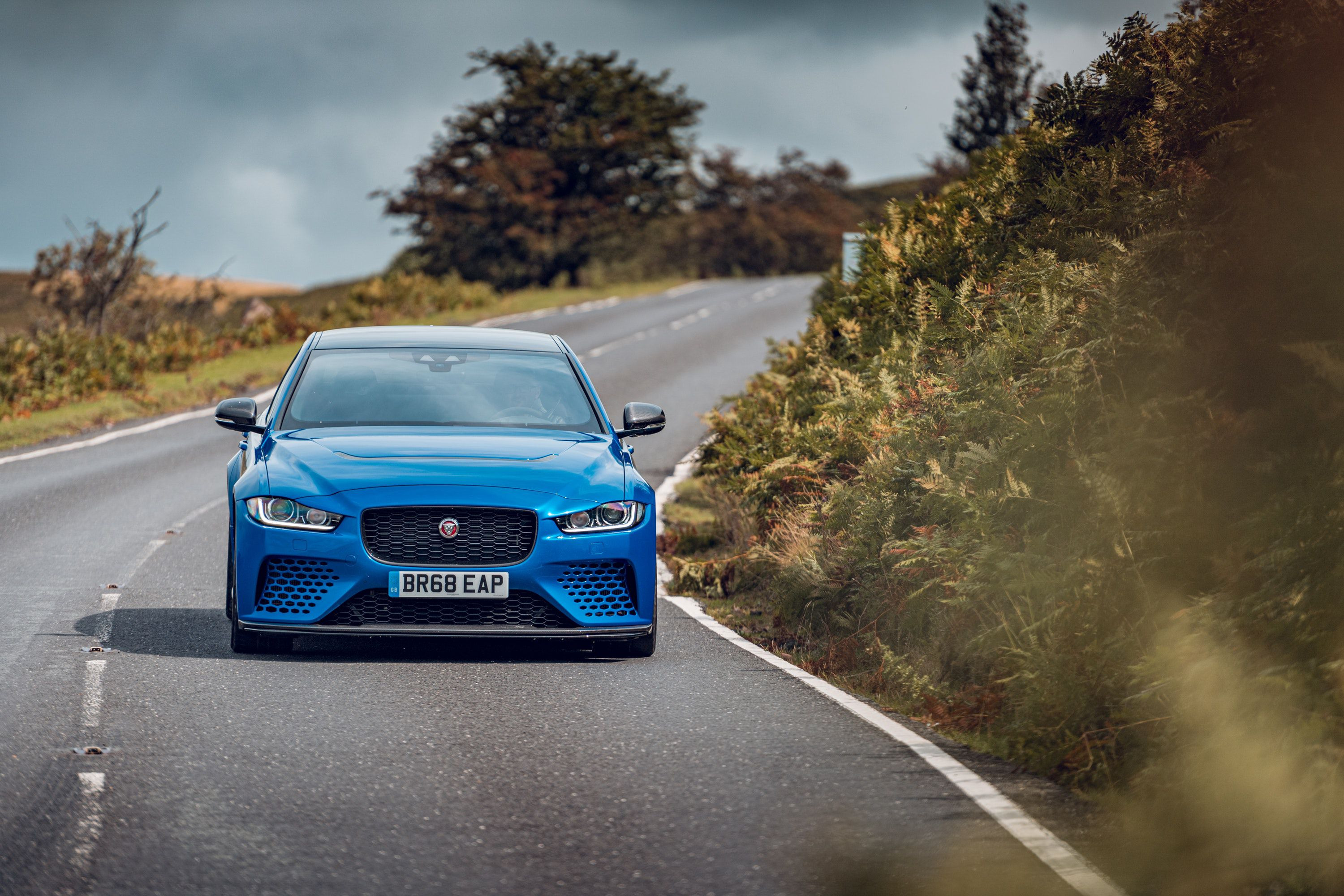 Front view of a blue jaguar XE SV driving on a road