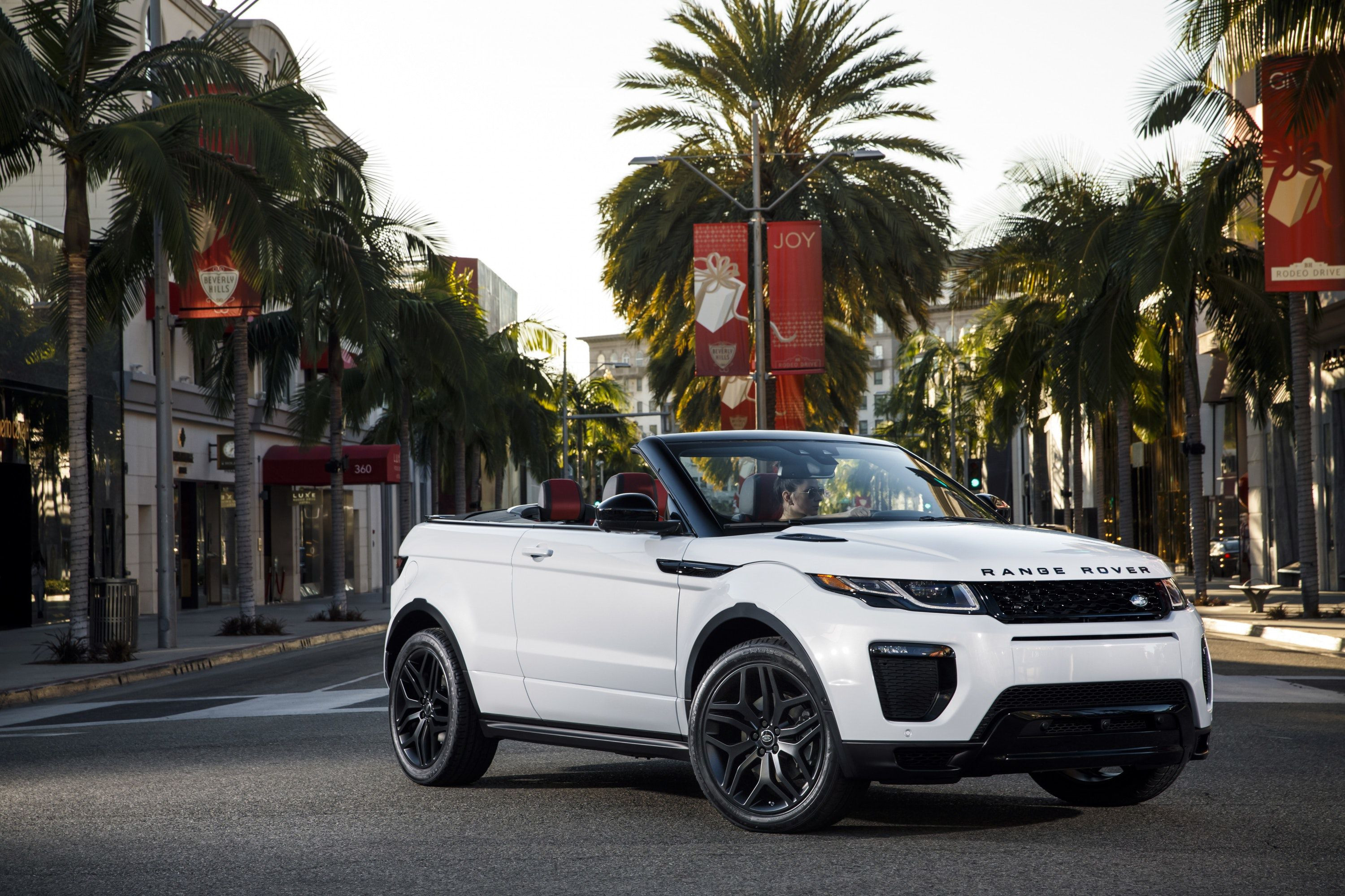 White Range Rover Evoque convertible driving through the city