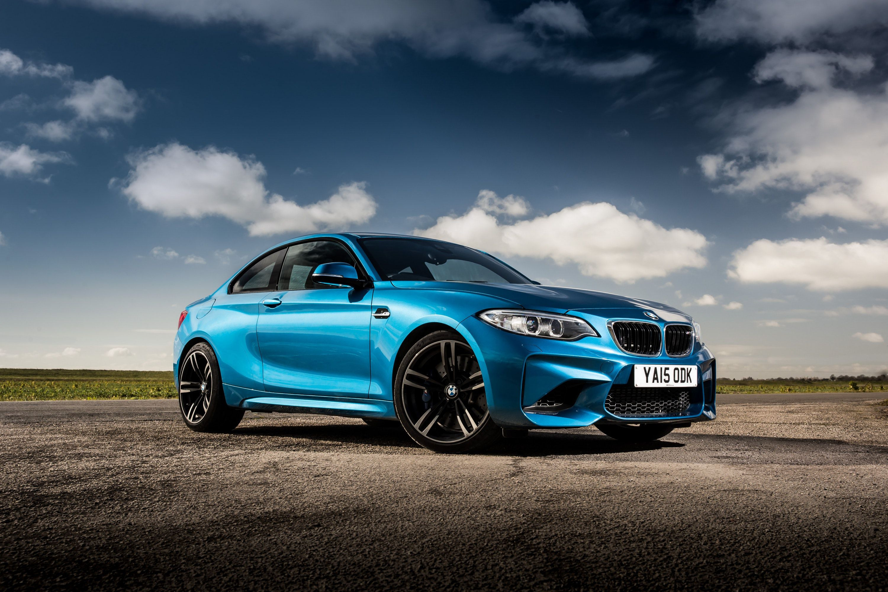 Blue BMW M2 3 door car with black alloy wheels