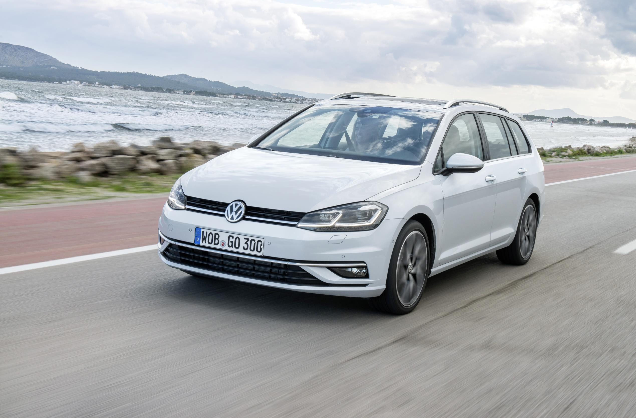 White Volkswagen Golf estate driving towards you two thirds side on