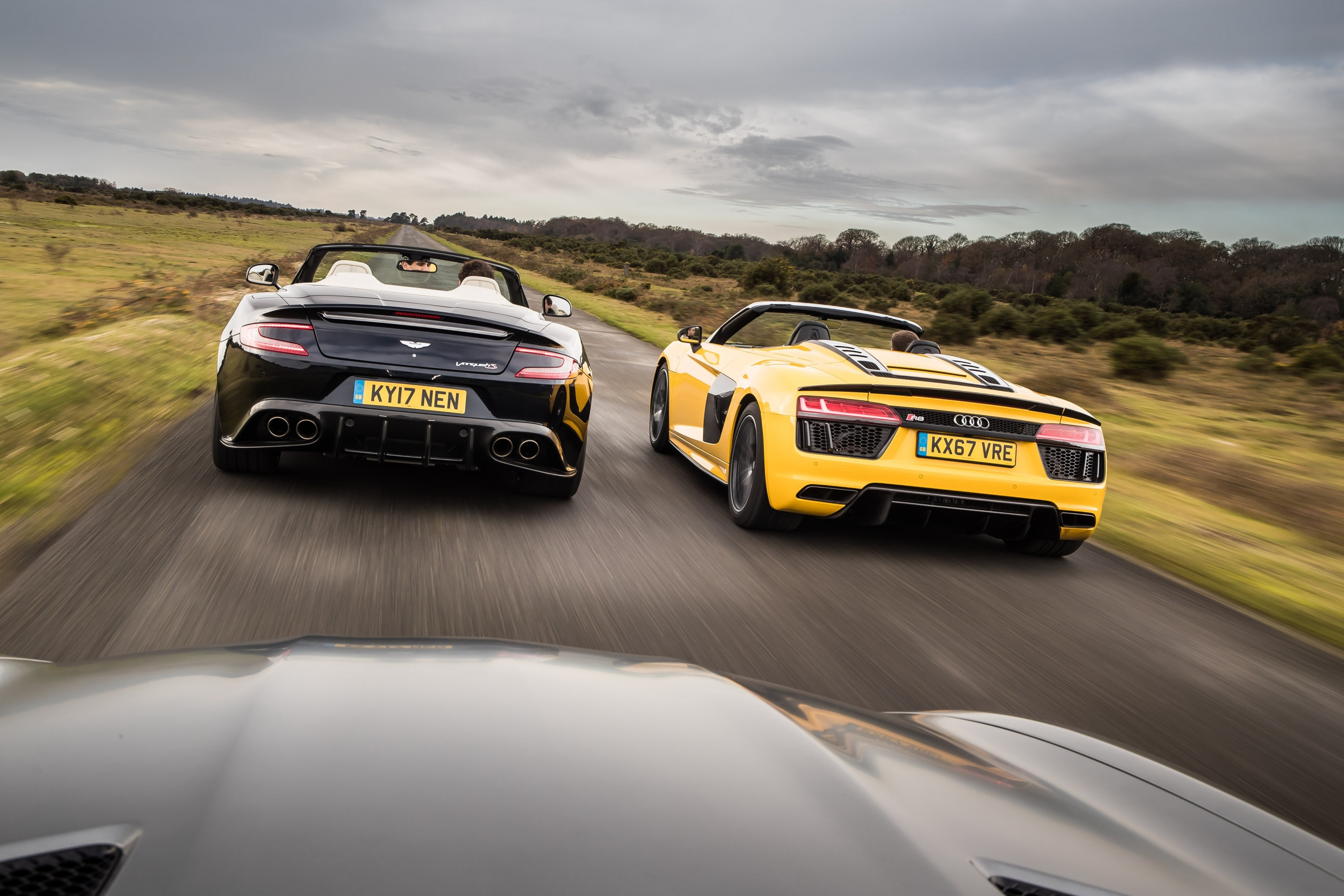 Aston Martin Vanquish and Audi R8 Spyder driving away