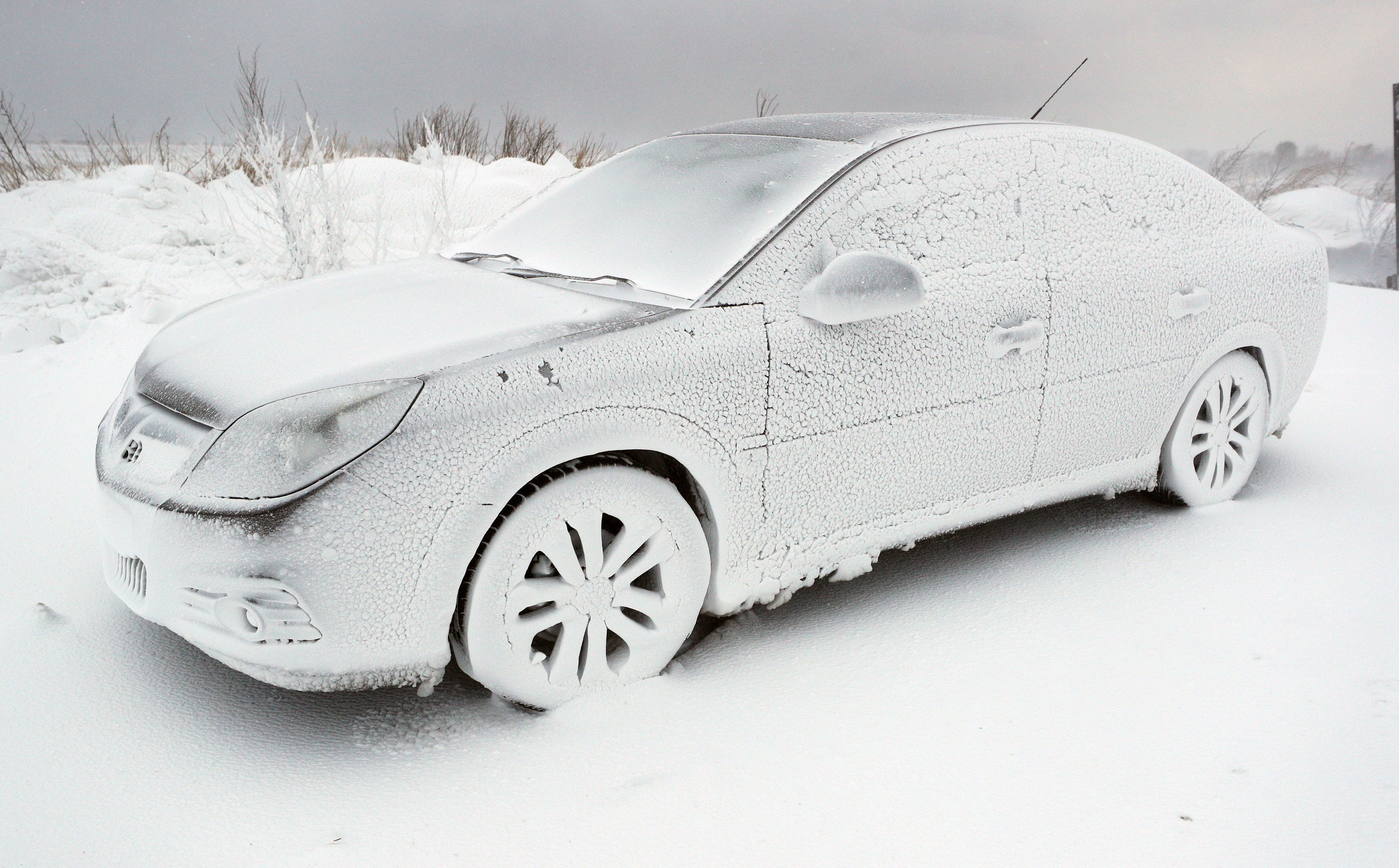 Car parked and absolutely covered in snow