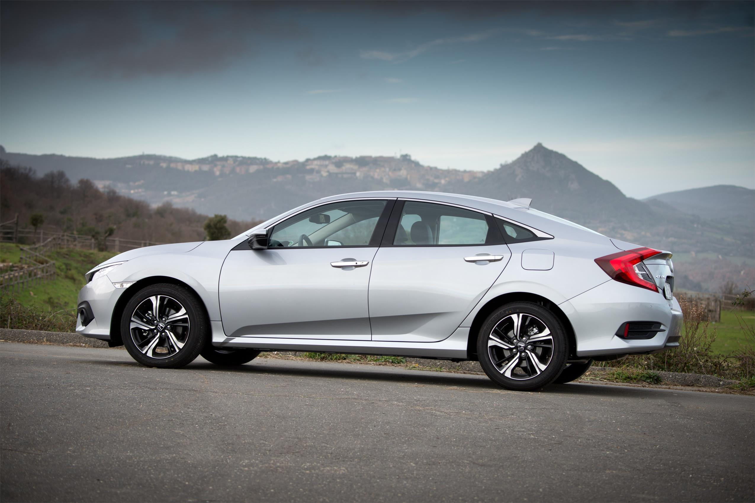 Silver Honda Civic Saloon parked side on with mountain scenery behind