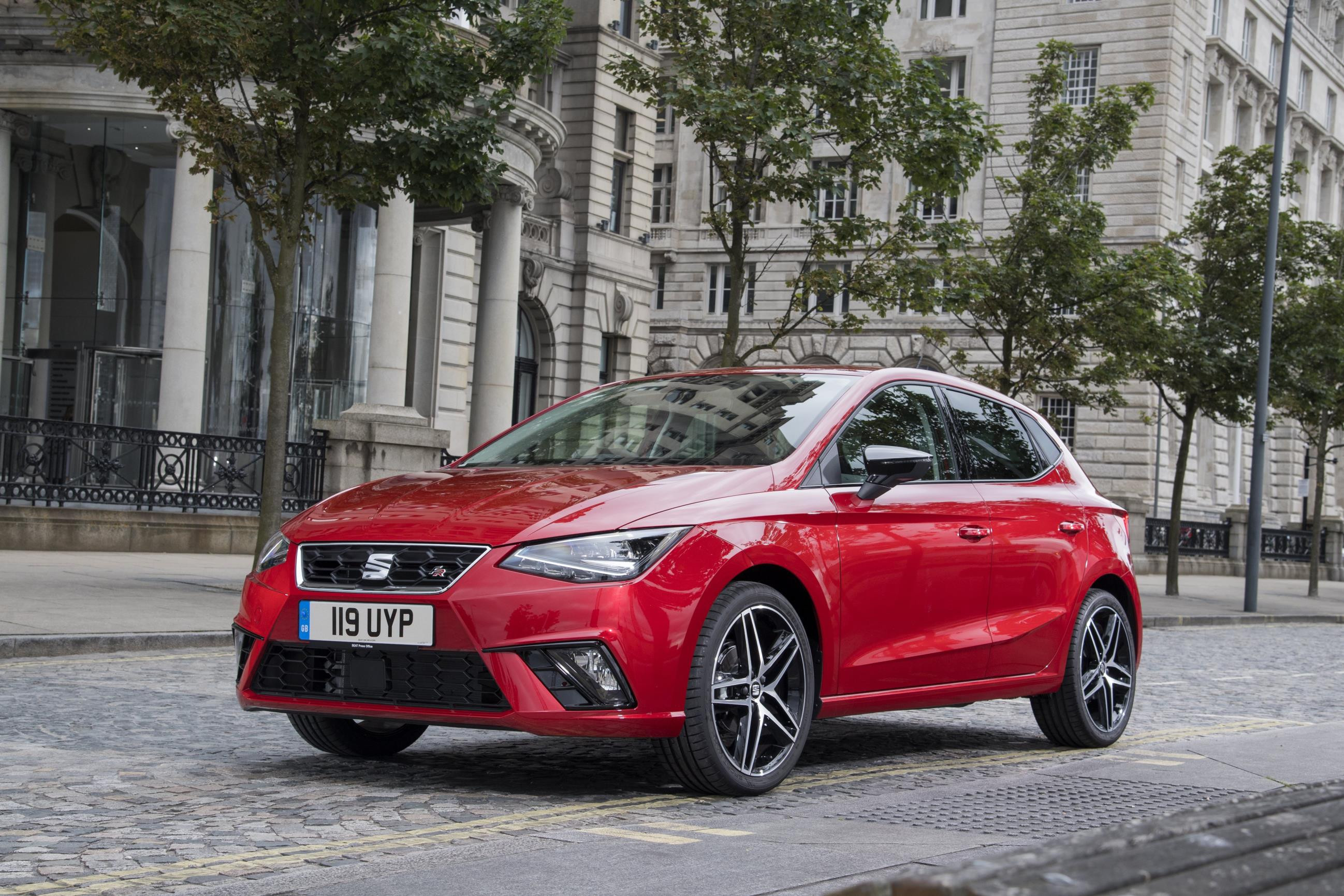 Red SEAT Ibiza parked on a leafy road