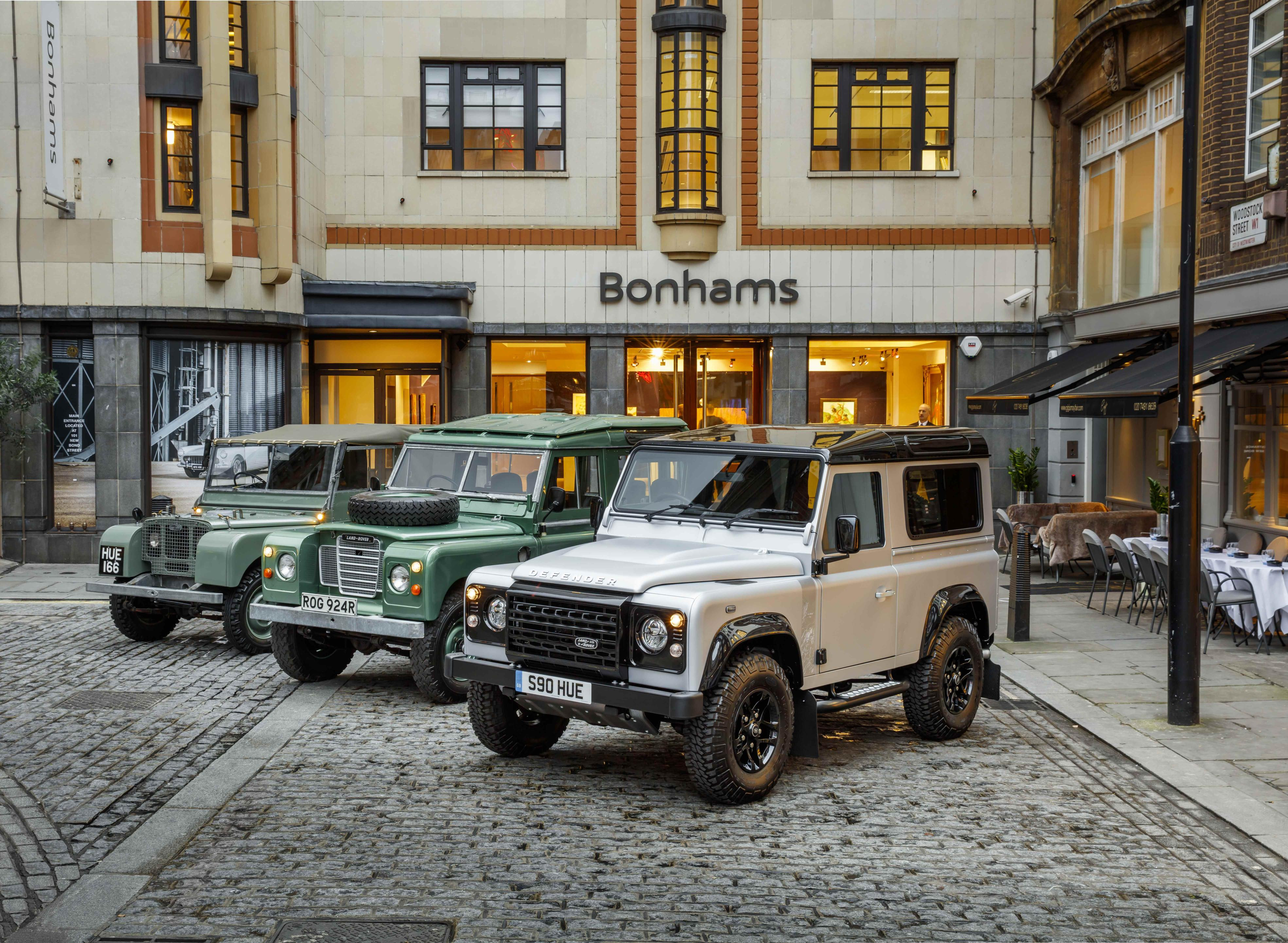 Lin-up of iconic Land Rover Defenders on a cobbled street