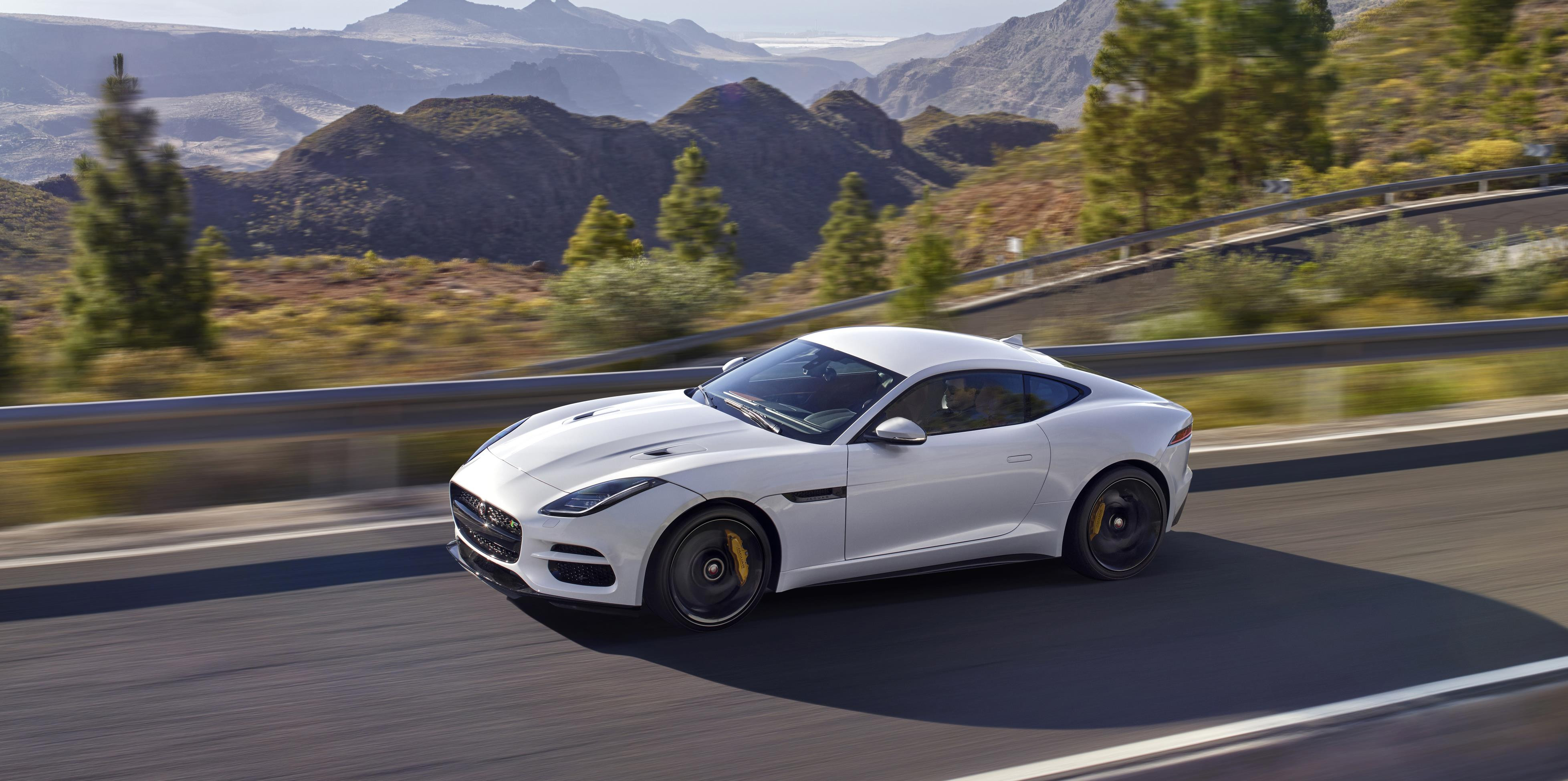 White Jaguar F-TYPE driving at speed and seen from the side and above