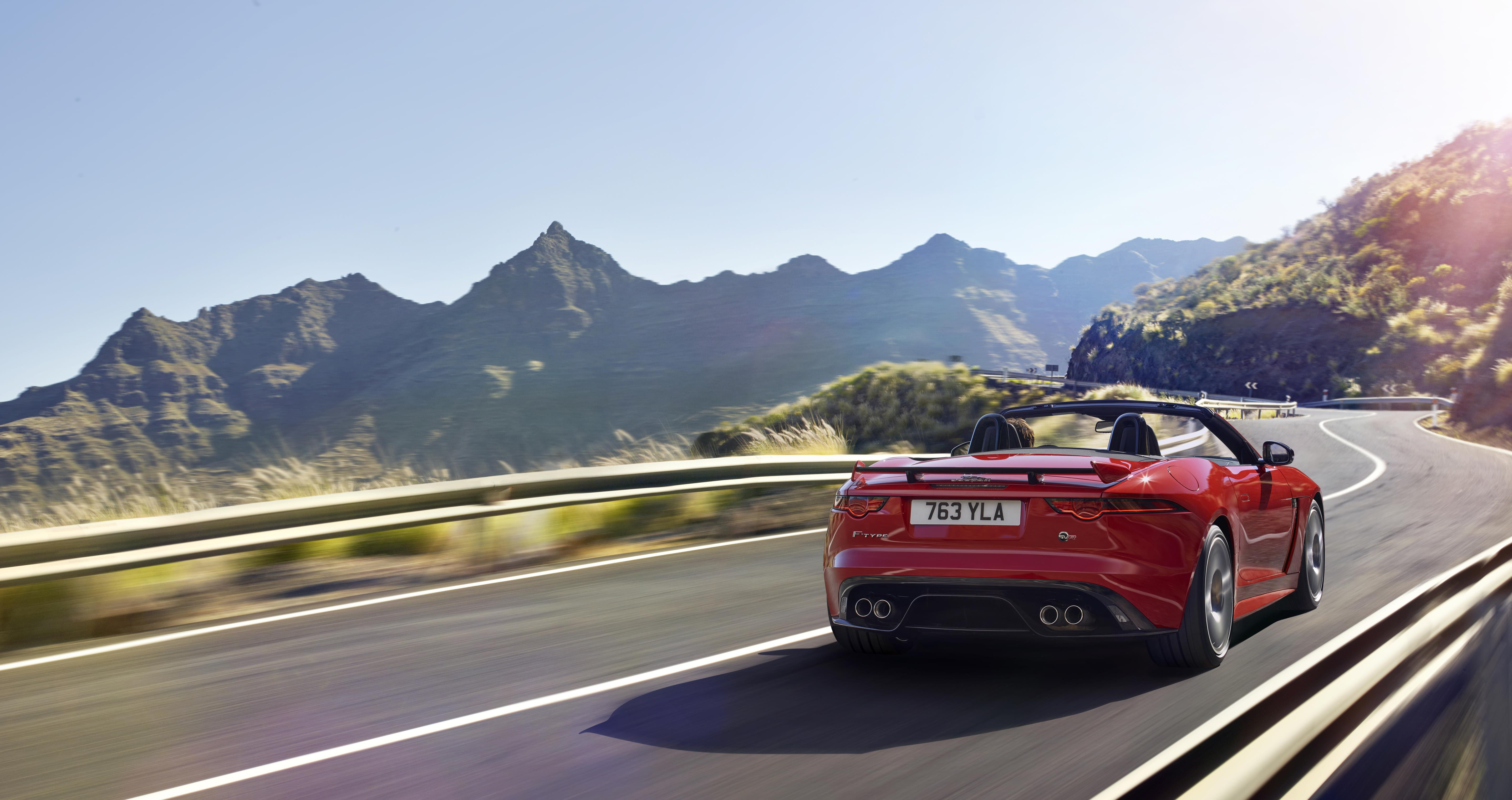 Red Jaguar F-Type convertible driving away from you in spectacular countryside