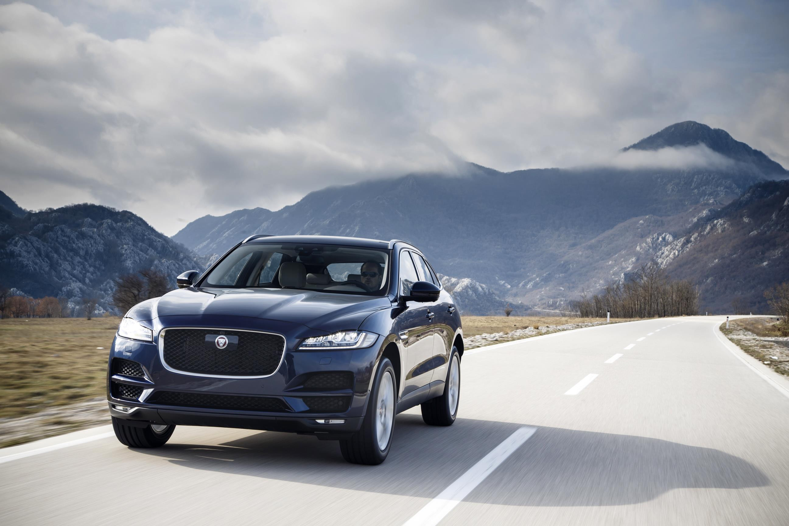Dark blue Jaguar F-Pace driving towards you on an isolated road