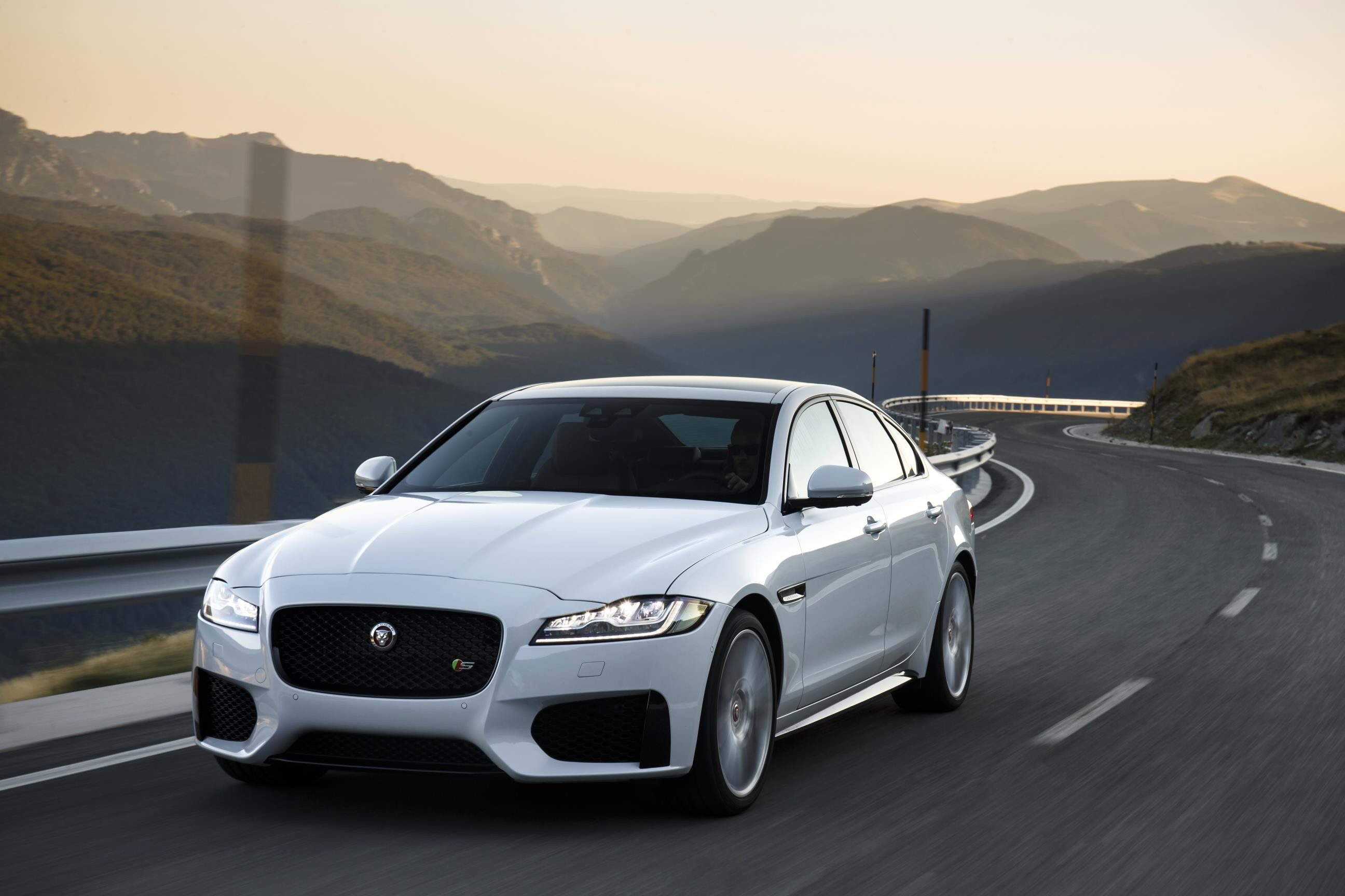 White Jaguar XF driving towards you