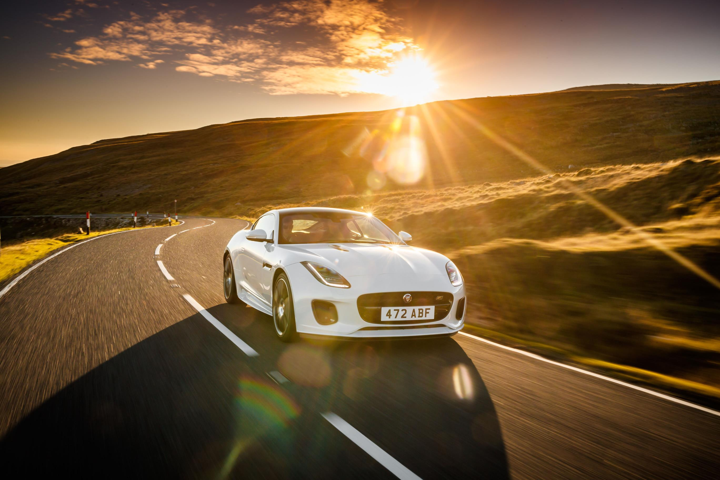 White Jaguar F-Type sports car driving towards you at sunset