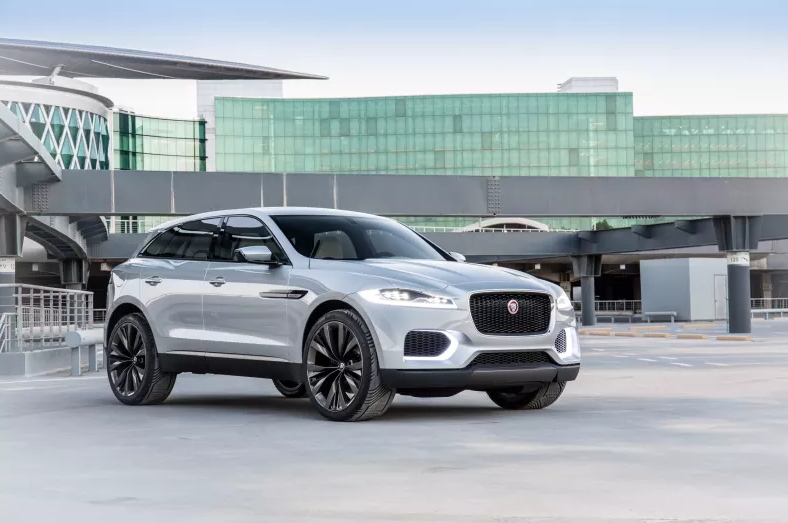 Bright silver Jaguar F-Pace parked two thirds on with a futuristic backdrop