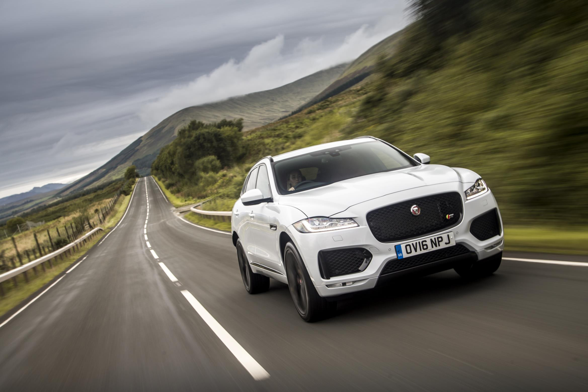White Jaguar F-Pace driving towards you at speed