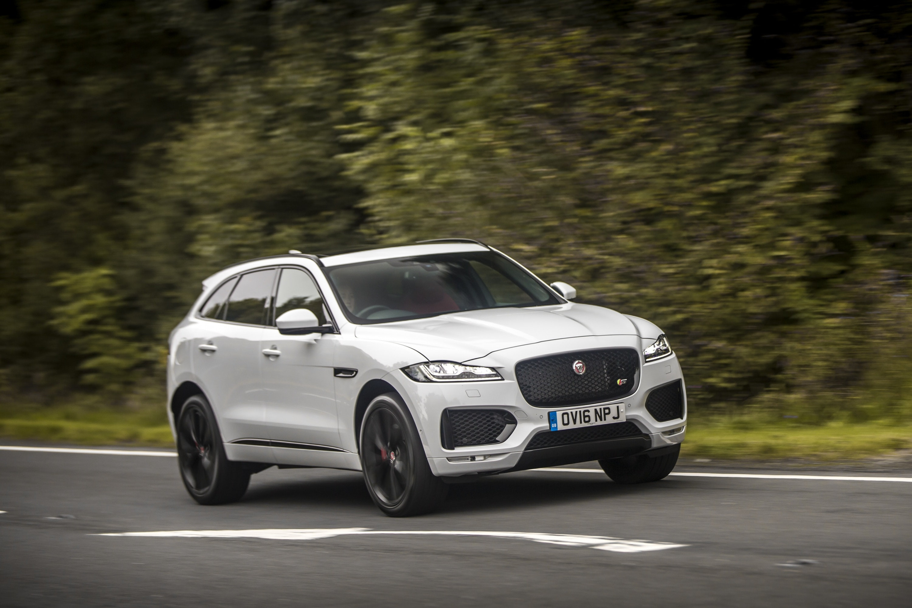 White Jaguar F-Pace at speed on a lane