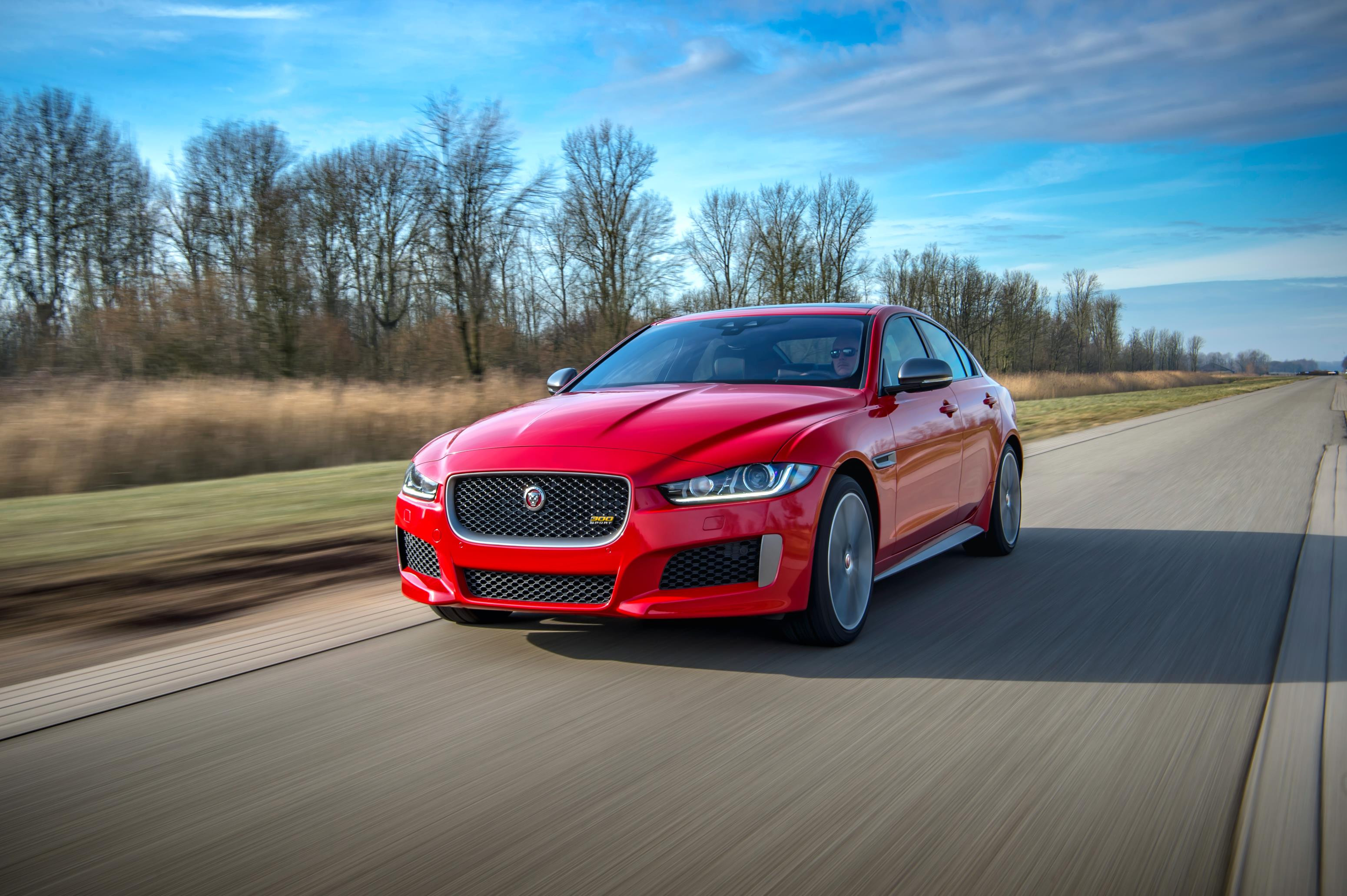 Red Jaguar XE driving towards you with a very blue sky