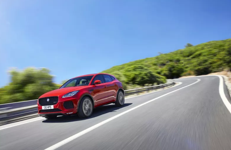 Red Jaguar E-PACE driving at speed round a bend