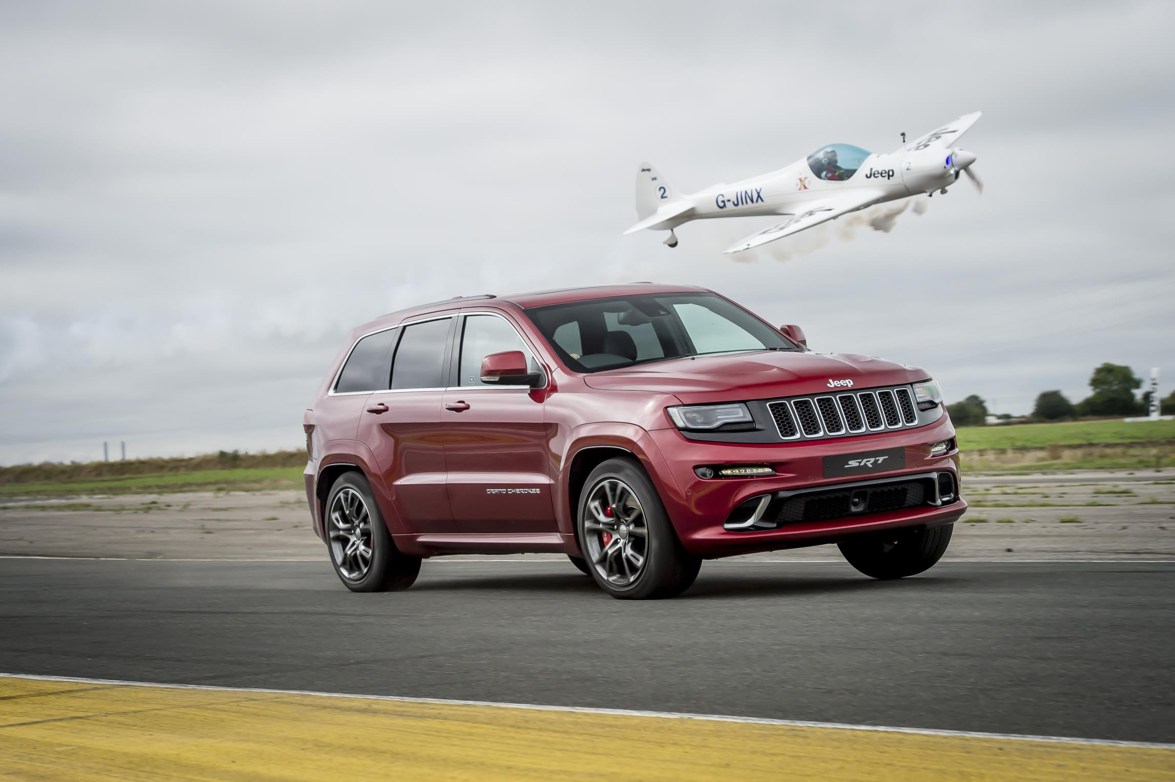 Red Jeep Grand Cherokee racing a single engined plane