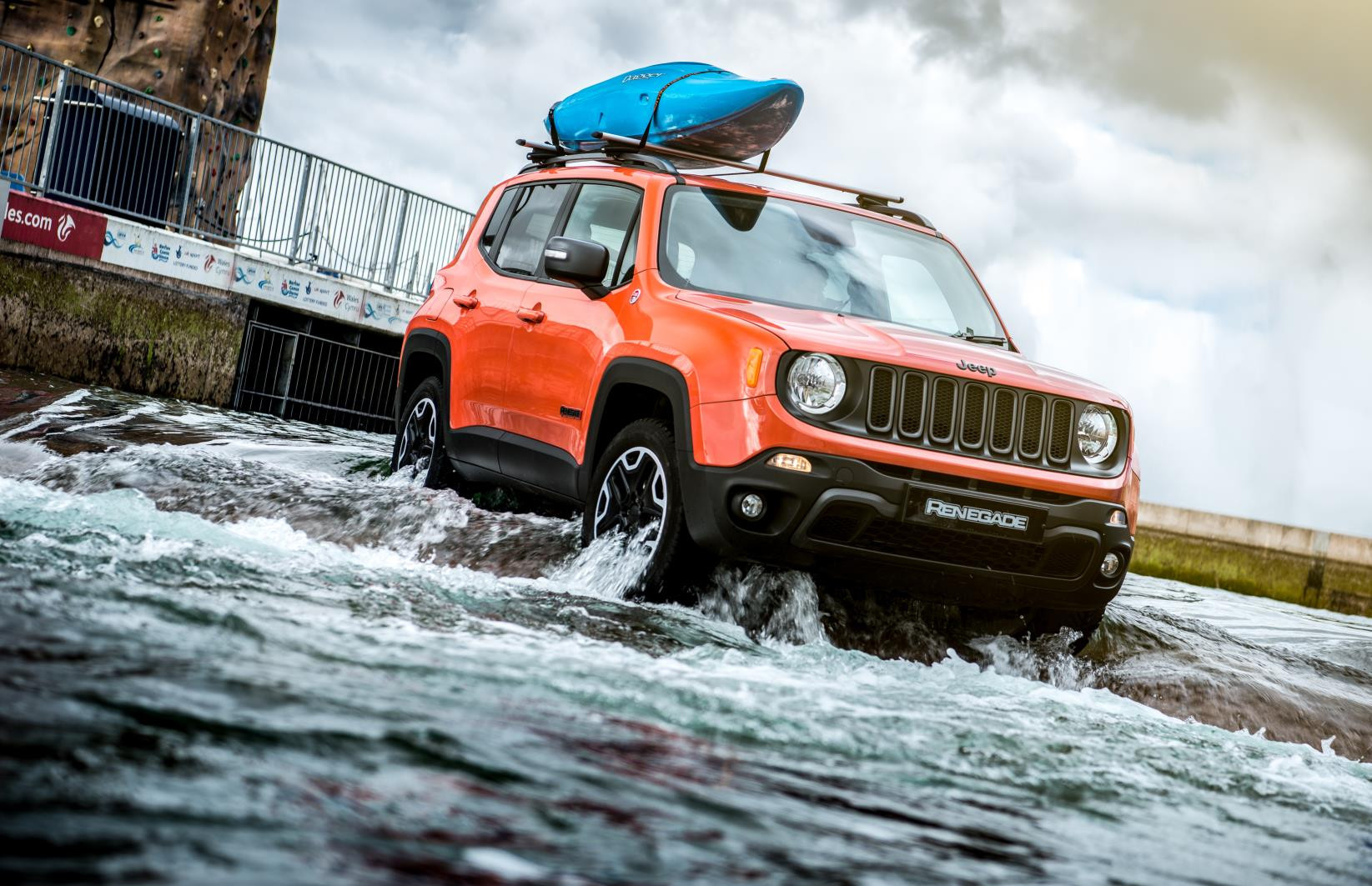 Orange Jeep Renegade crossing a weir with a canoe on the roof