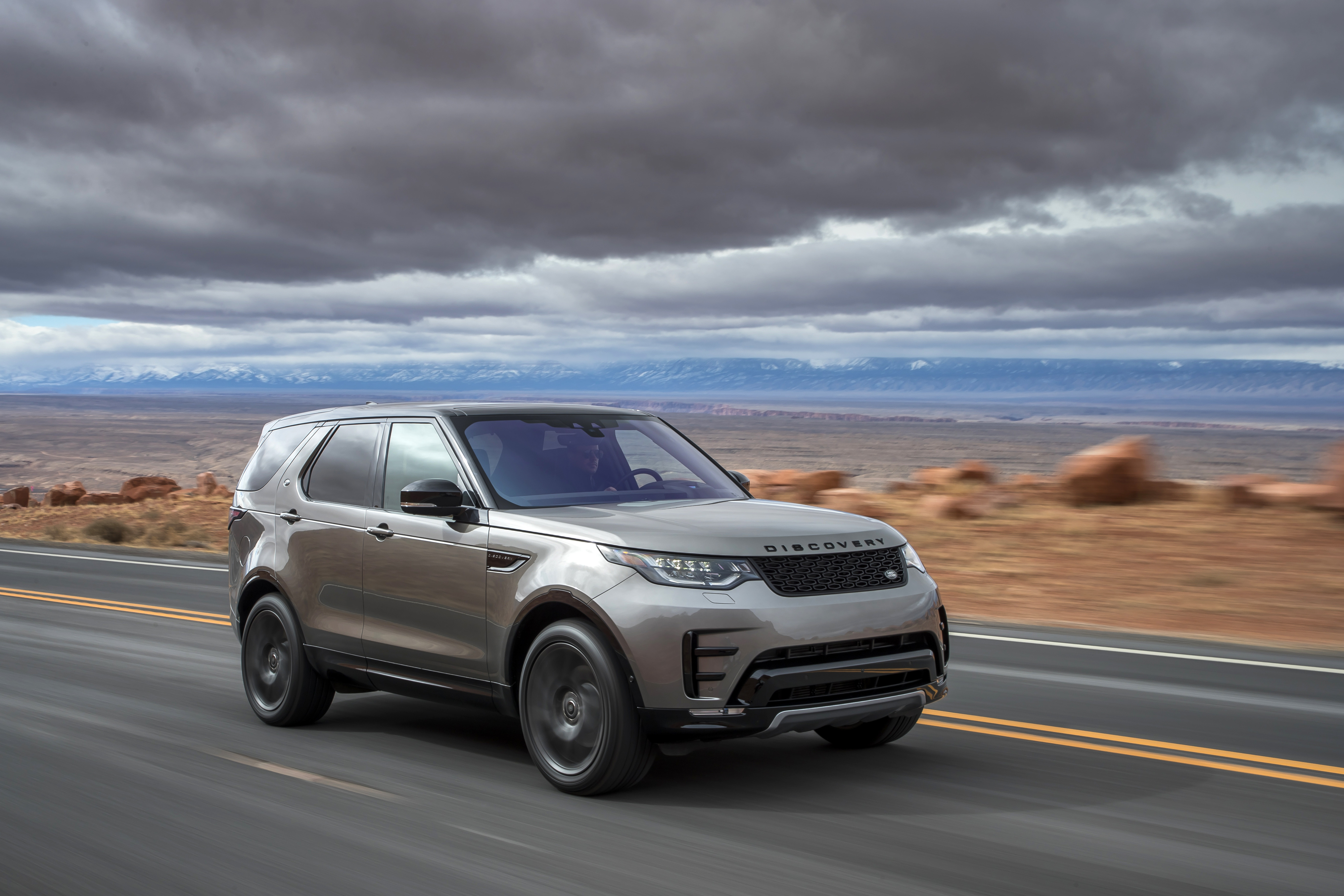 Pale gold Land Rover Discovery driving at speed side on to you
