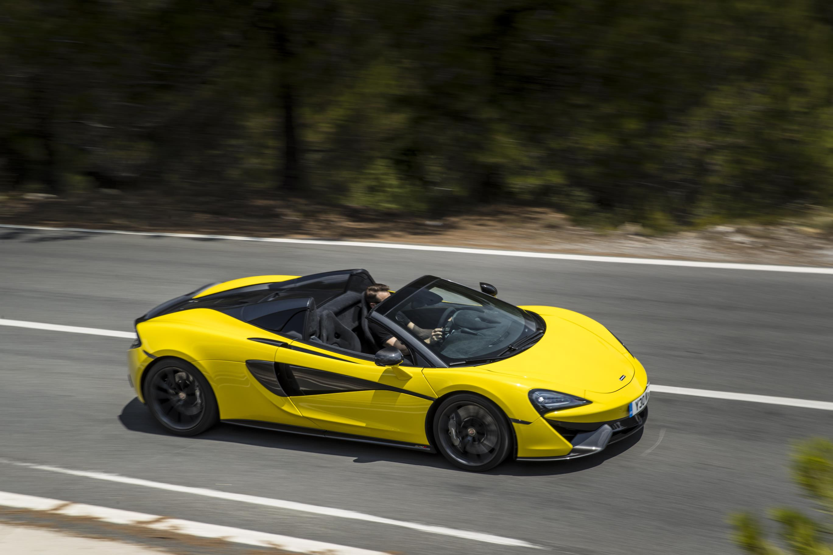 Bright yellow McLaren 570S driving down country lane