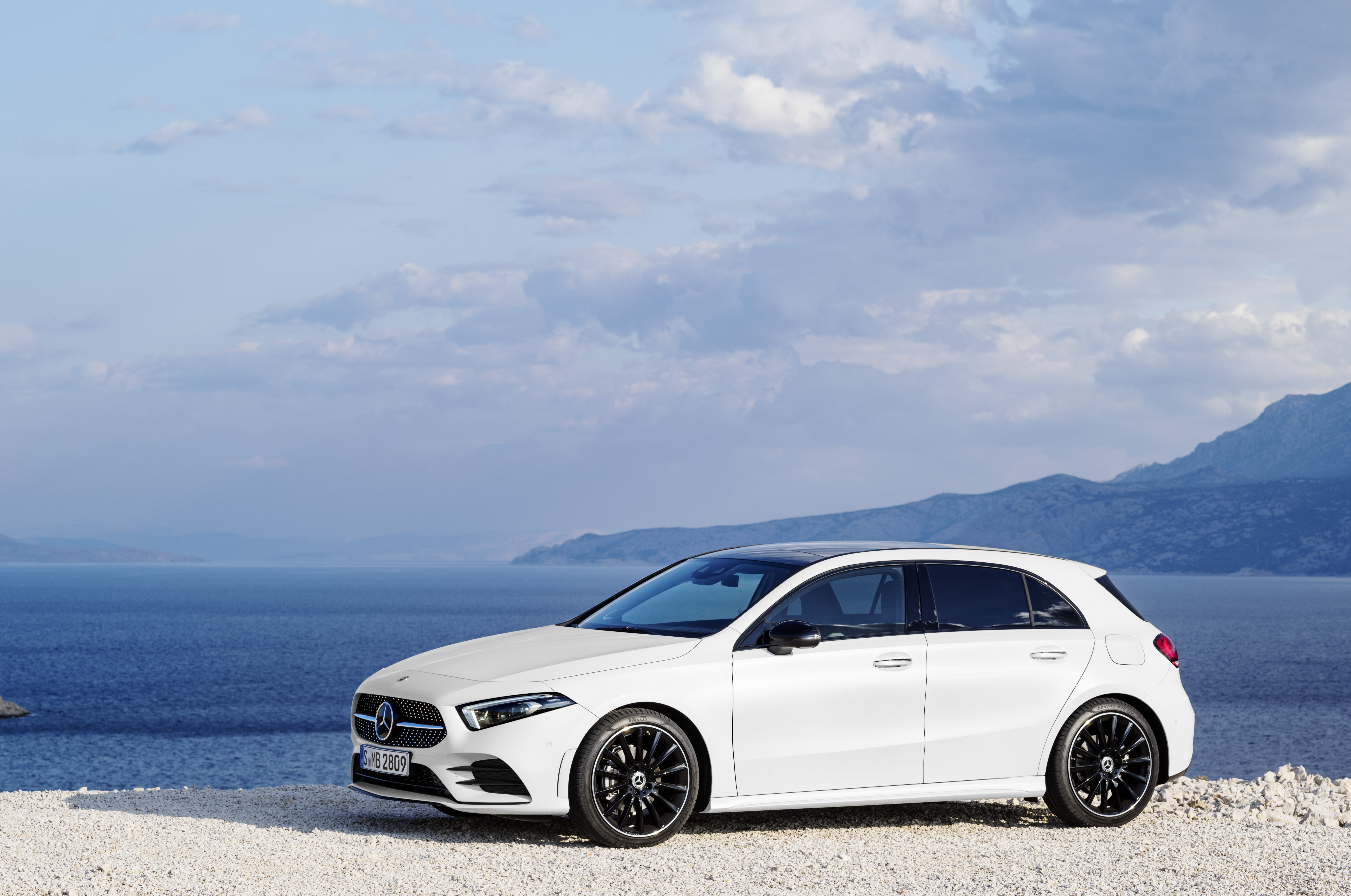 White Mercedes Benz A Class parked side on by the sea