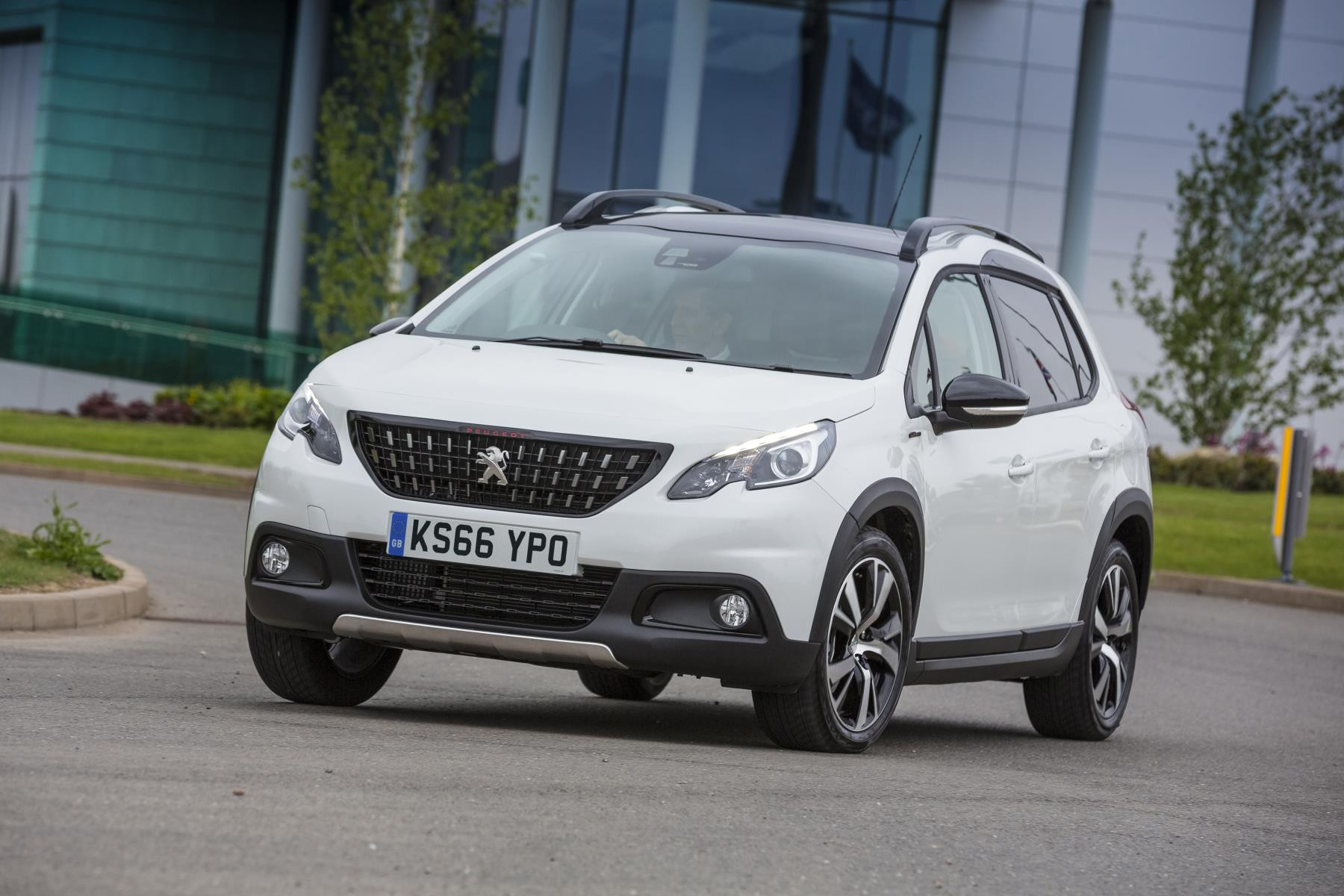 White Peugeot 2008 SUV driving towards you round a corner