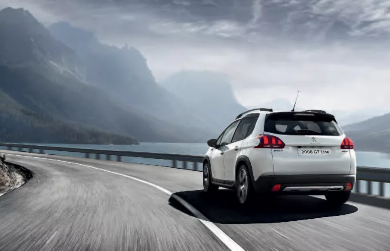 White Peugeot 2008 SUV seen from behind speeding around a bend by the sea