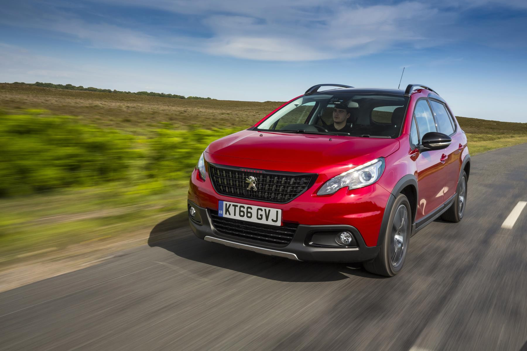 Red Peugeot 2008 SUV driving toward you down a lane