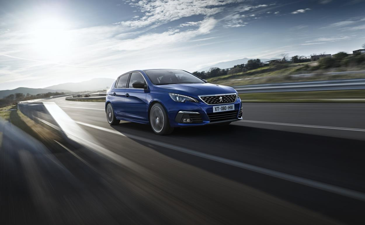 Bright blue metallic Peugeot 308 driving at speed round a bend
