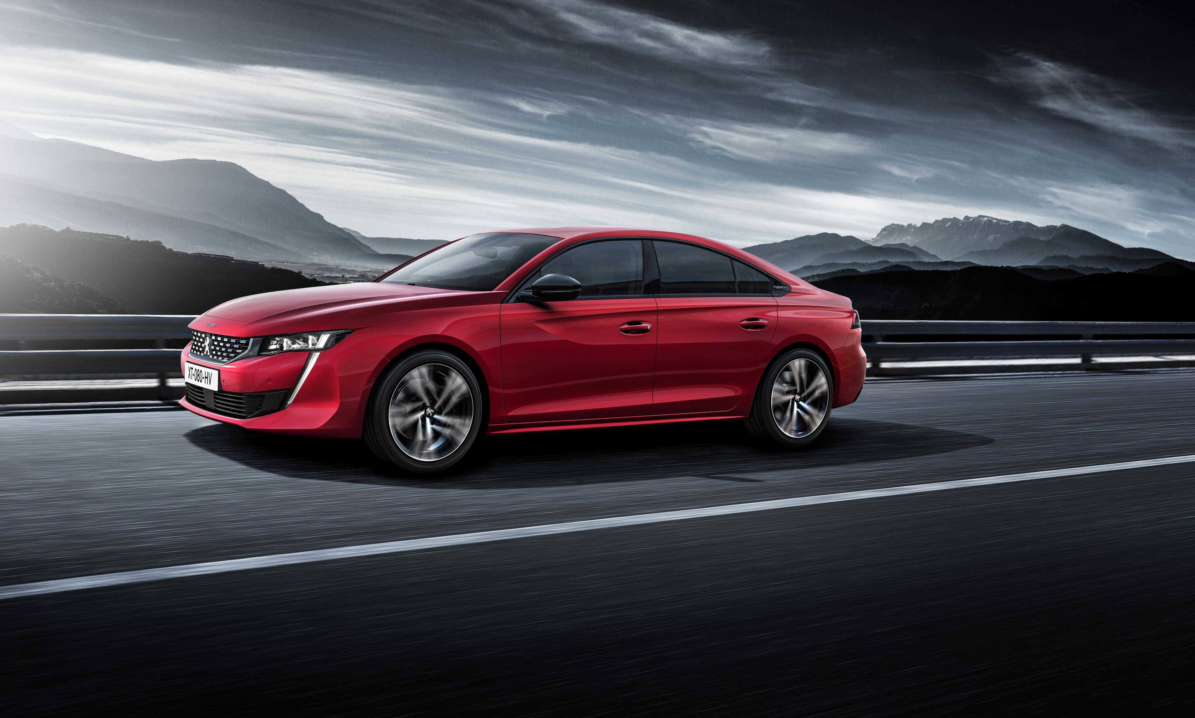 Red Peugeot 508 with dramatic backdrop