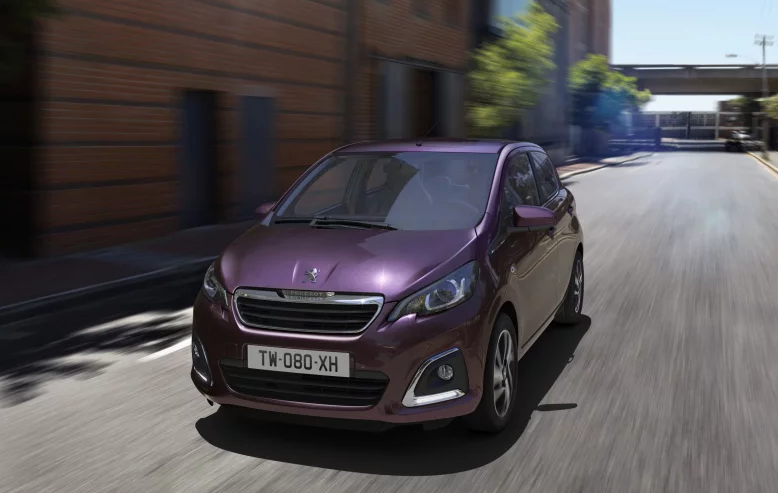 Purple Peugeot 108 whizzing down a road towards you
