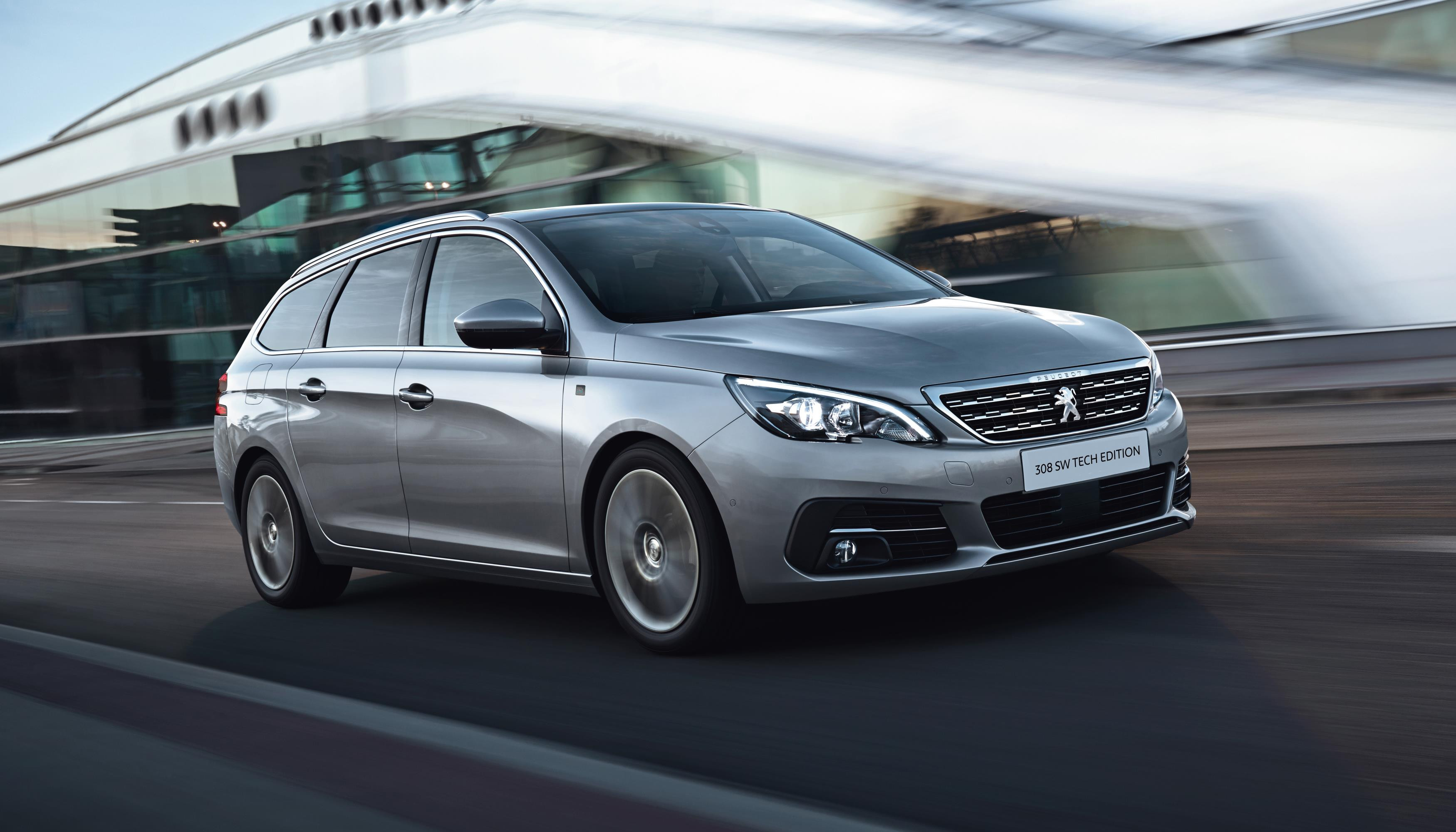 Silvery grey Peugeot 308 SW driving towards you at speed