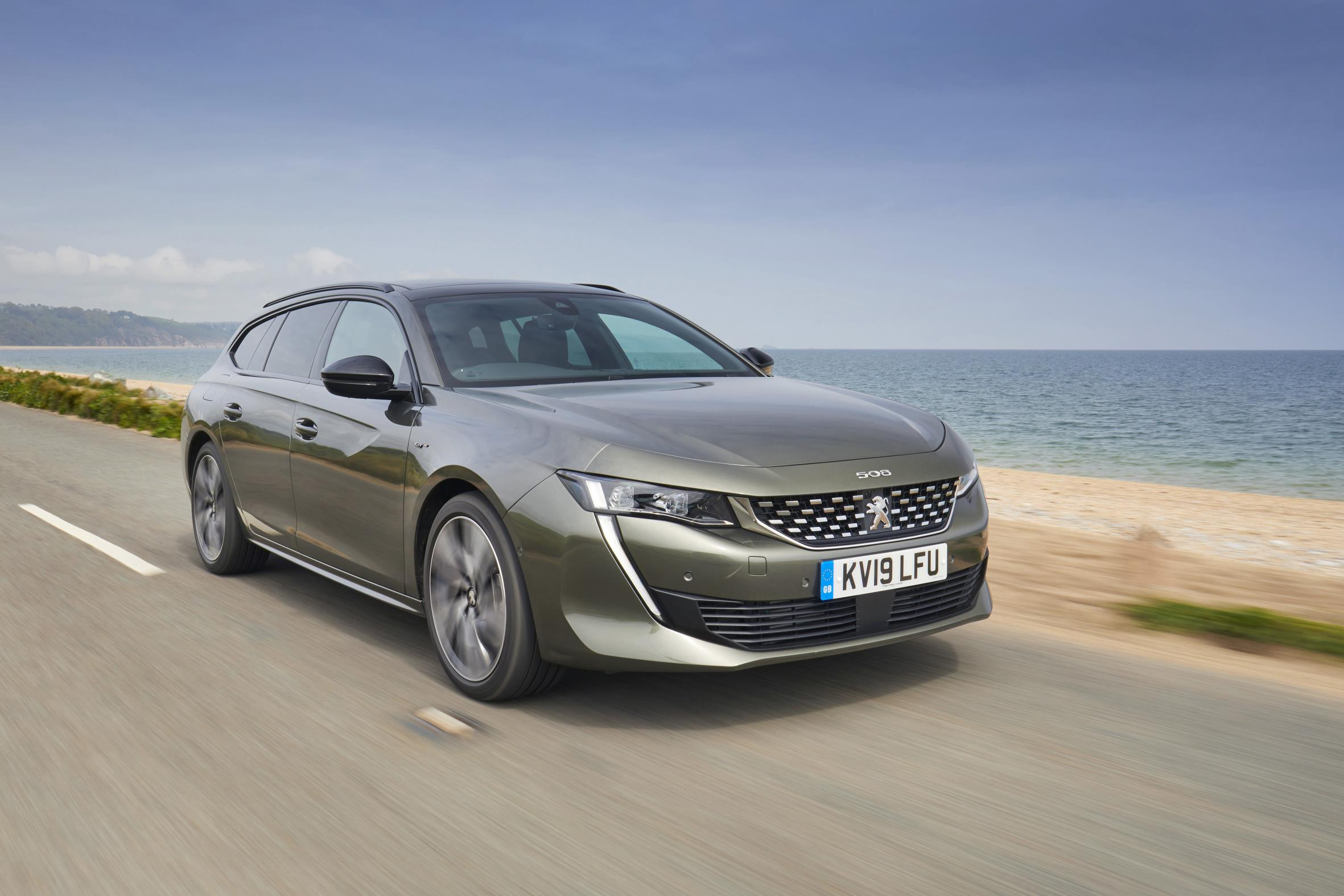 Metallic grey Peugeot 508 SW driving towards you on a coast road