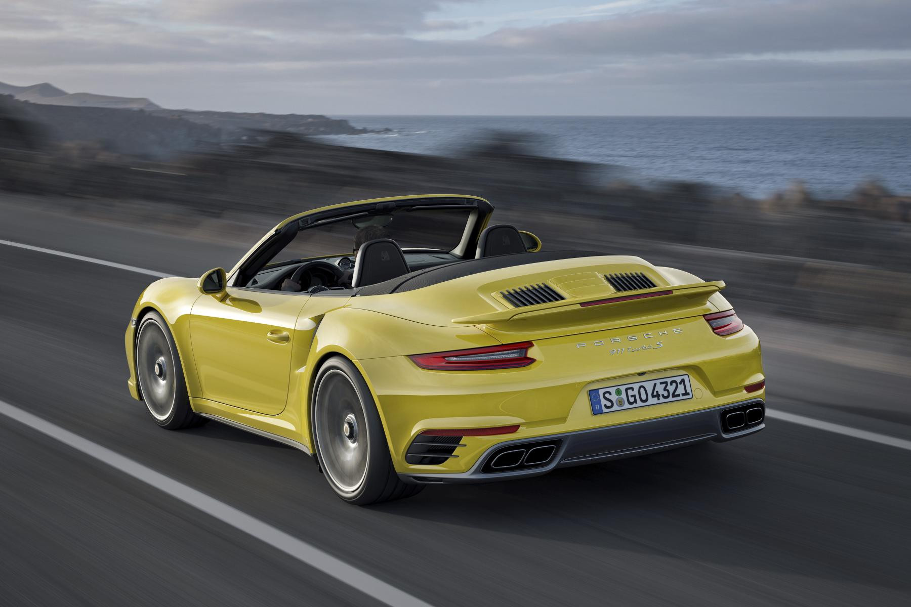 Pale yellow Porshe 911 convertible driving away from you