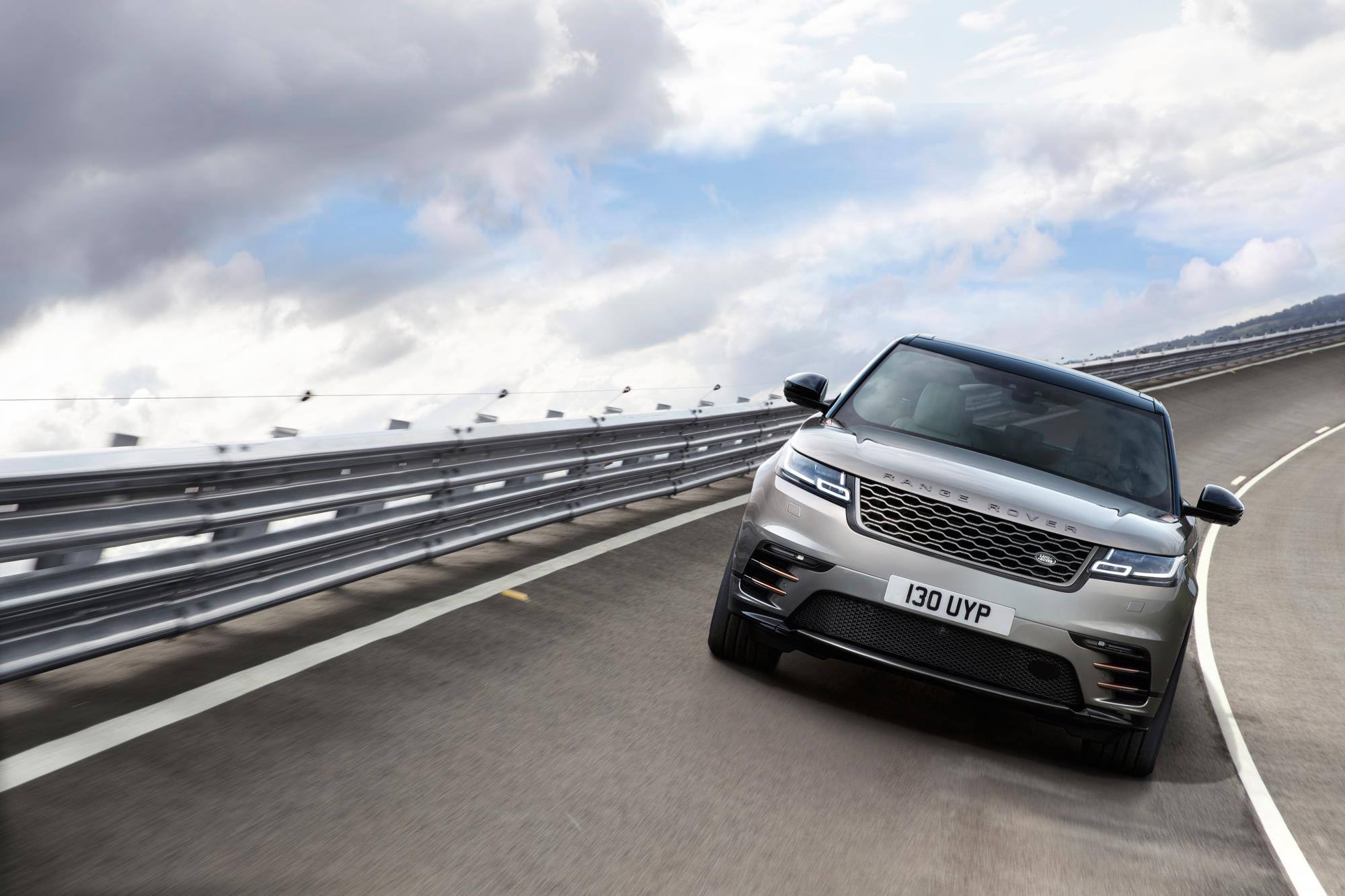 Metallic tauper Range Rover velar driving towards you