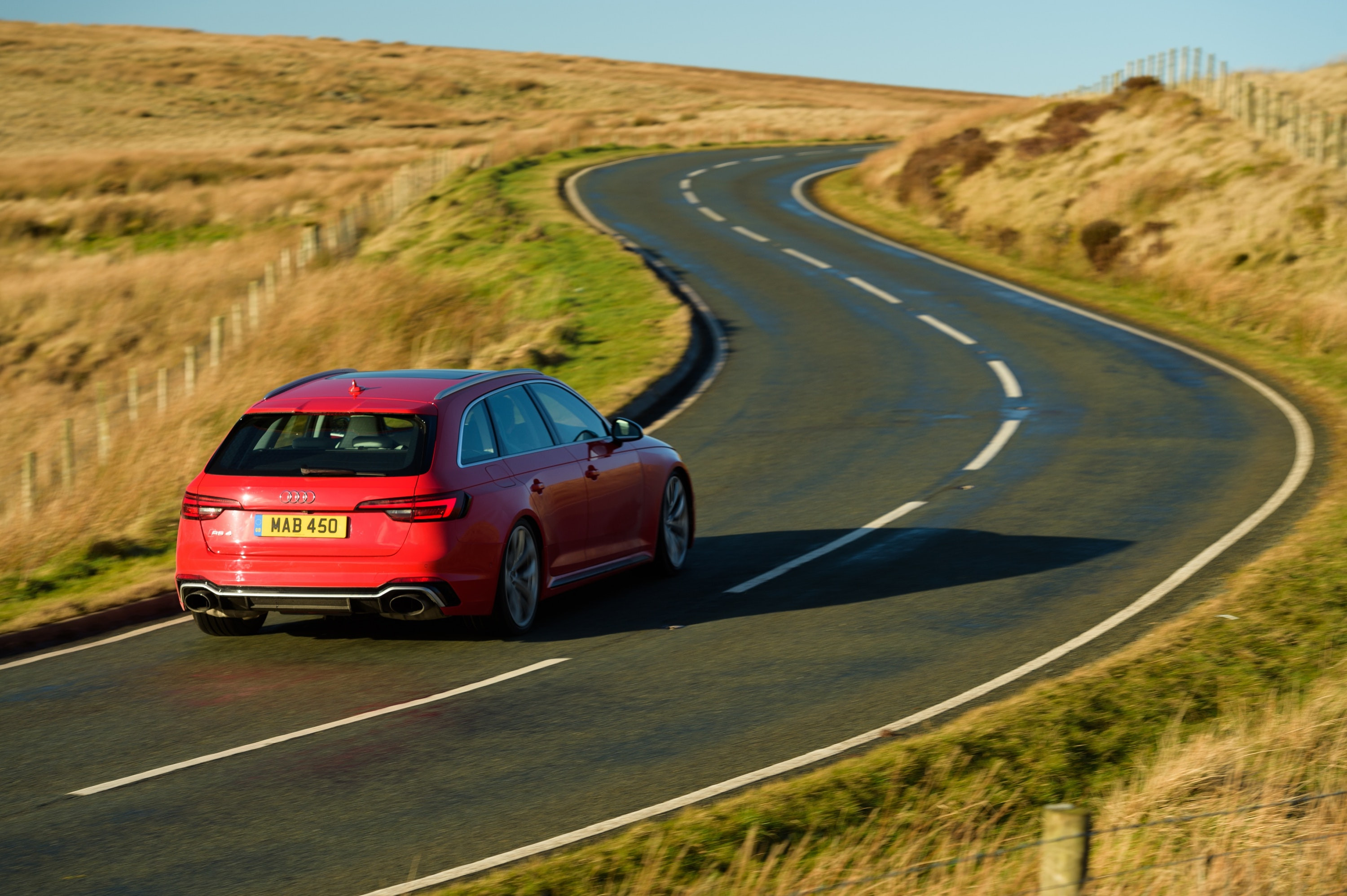 Winding lane with red Audi RS4 Avant driving away from you