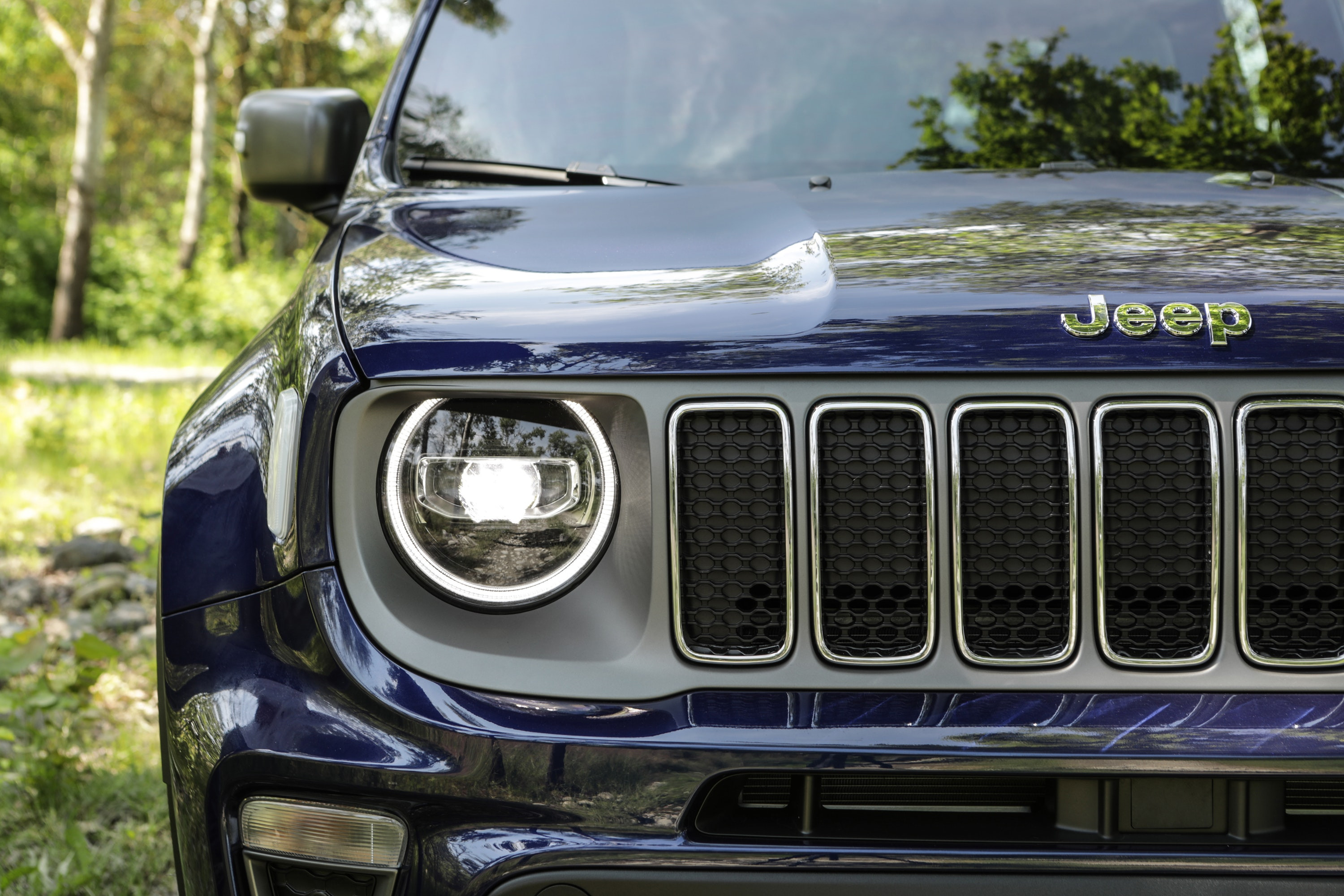 Half the front of a blue Jeep Renegade