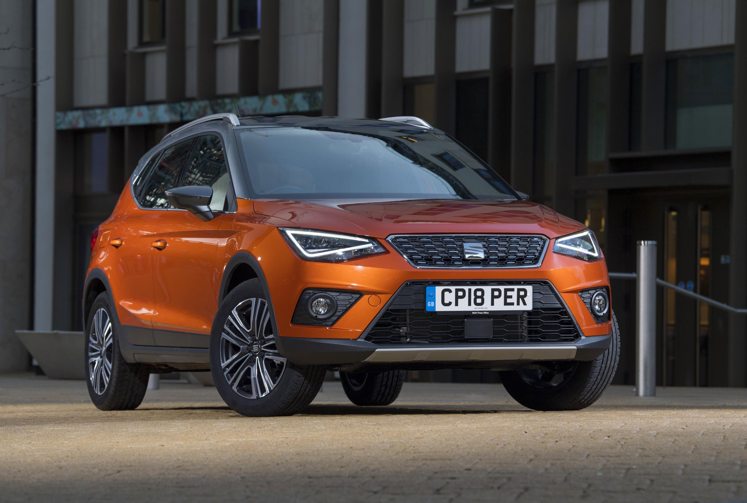 SEAT Arona in bright orange metallic parked facing you