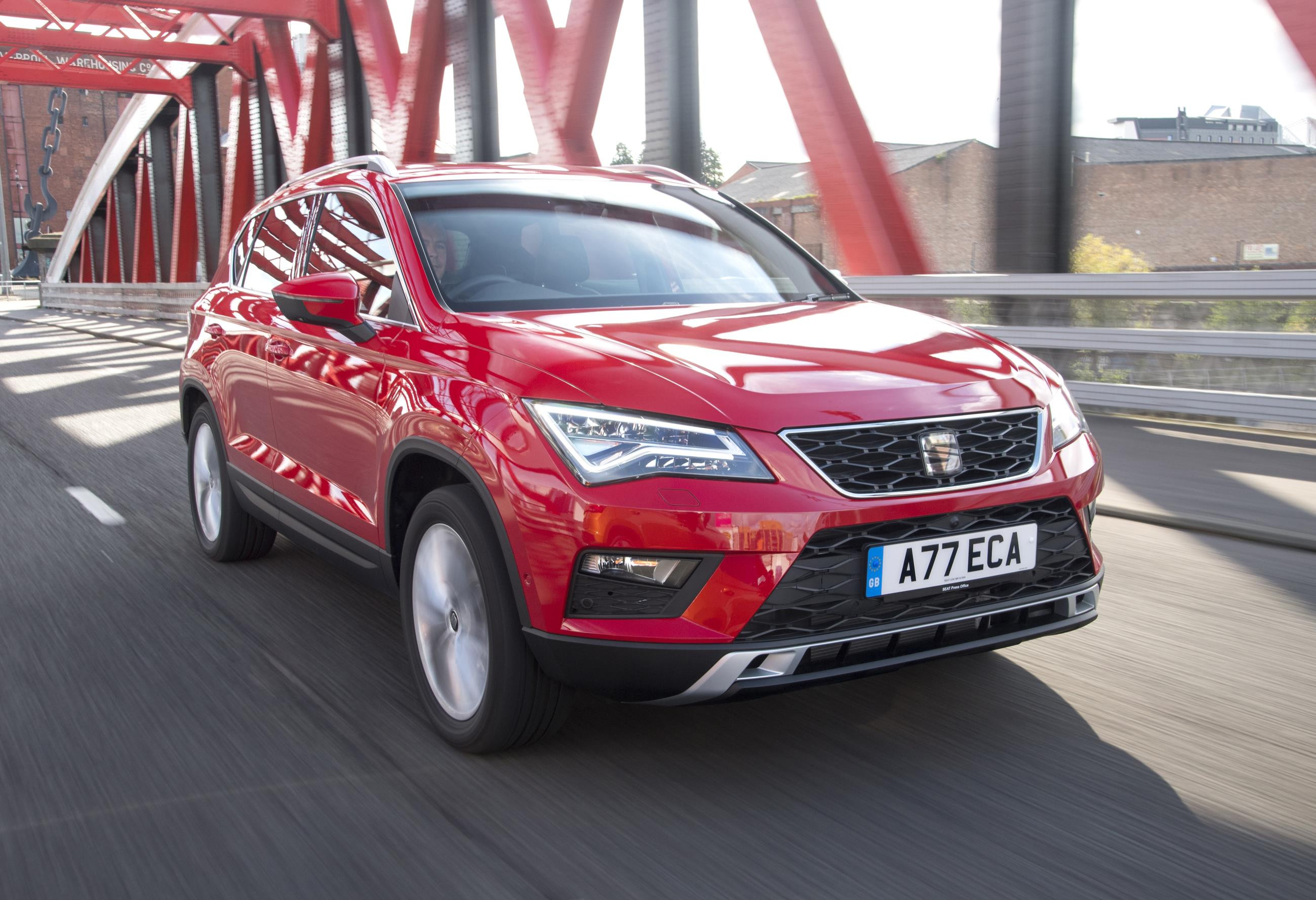 Red SEAT Ateca driving over a red suspension bridge